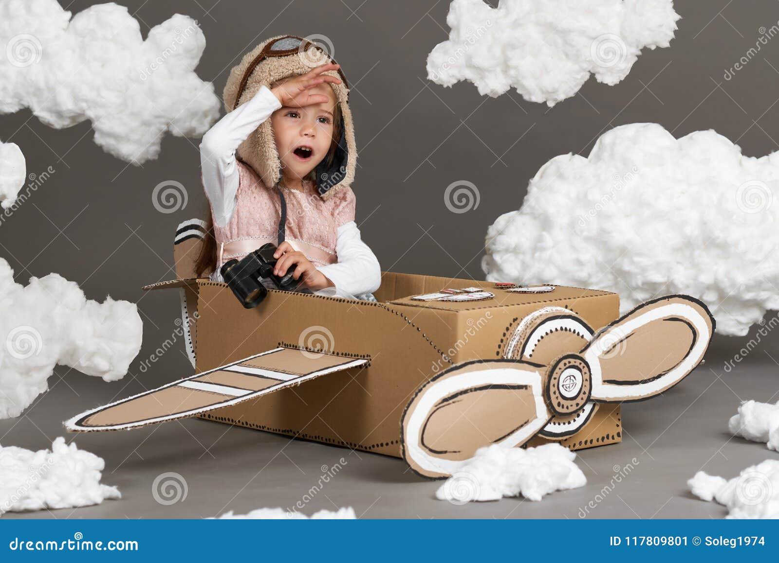 La muchacha del niño juega en un aeroplano hecho de la caja de cartón y de sueños de hacer piloto, nubes de la algodón en un back