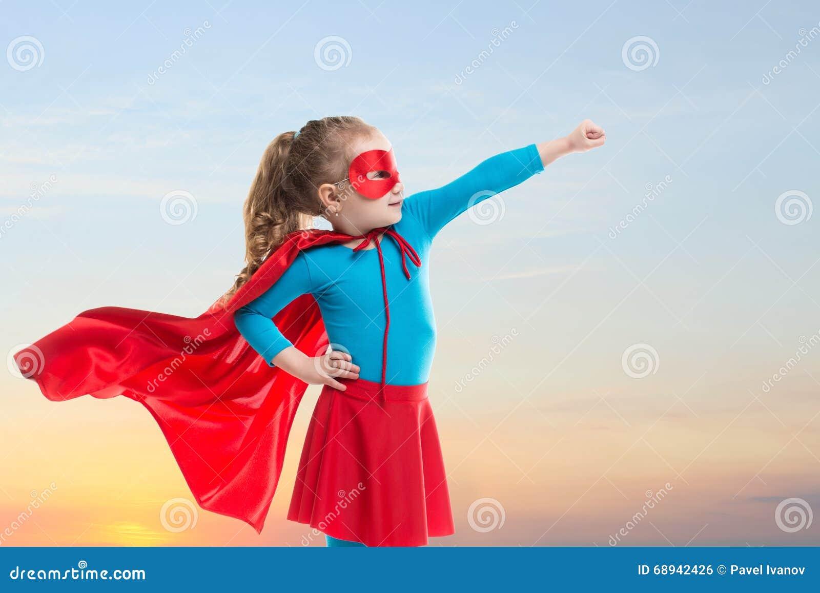La muchacha del pequeño niño juega al super héroe Niño en el fondo del cielo de la puesta del sol