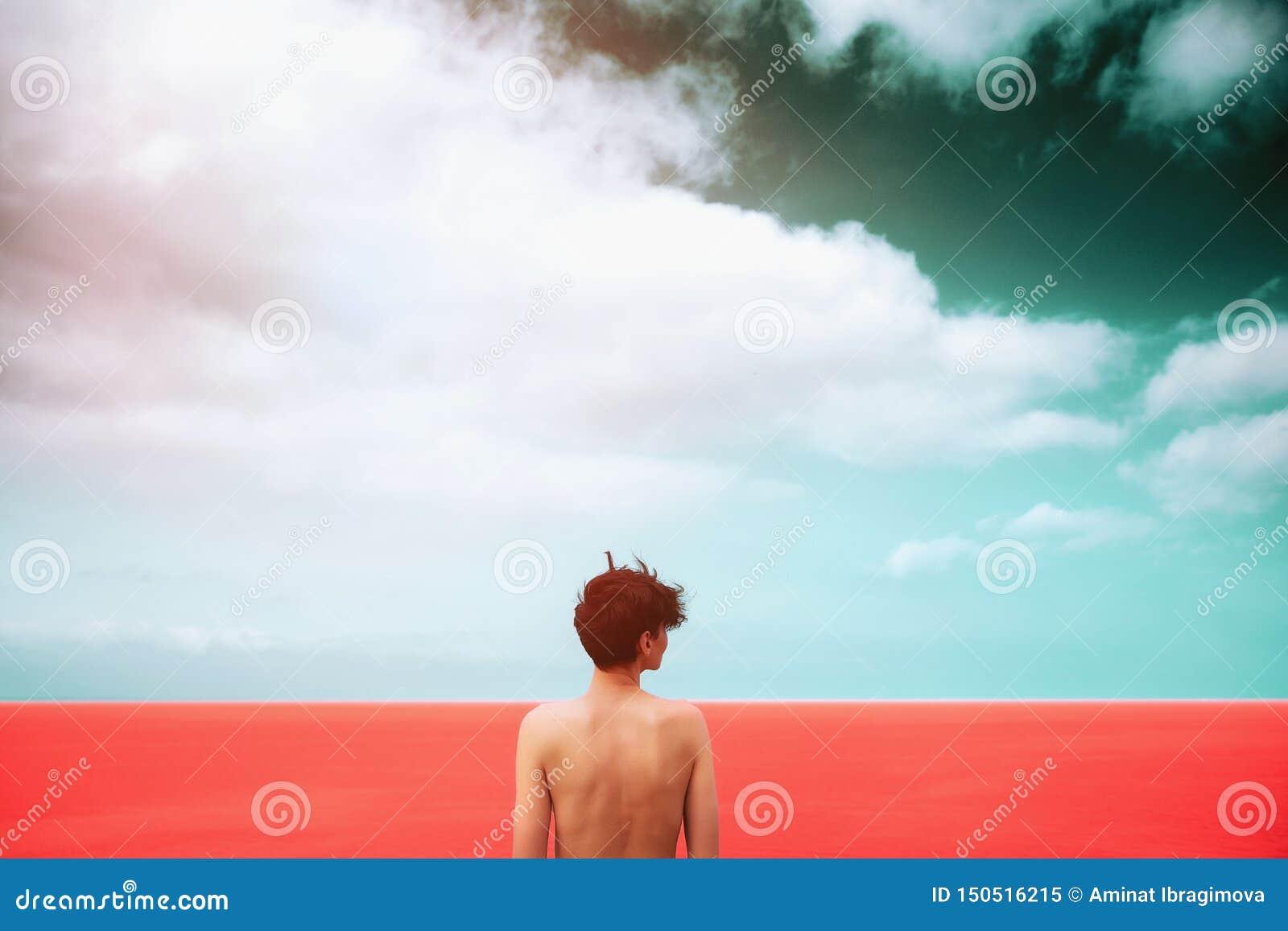 La muchacha delgada con un desnudo hermoso está retrocediendo en el mar de coral vivo Cielo oscuro con las nubes Unidad con la na