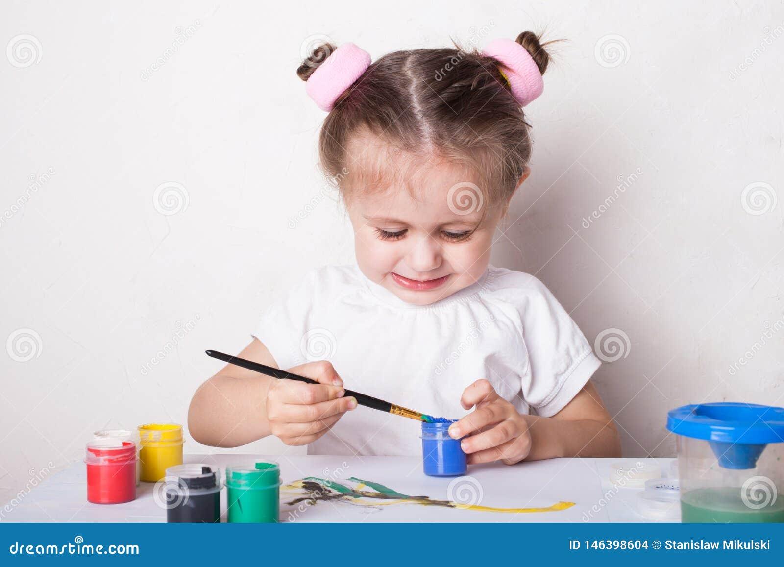 La muchacha dibuja en pinturas del color