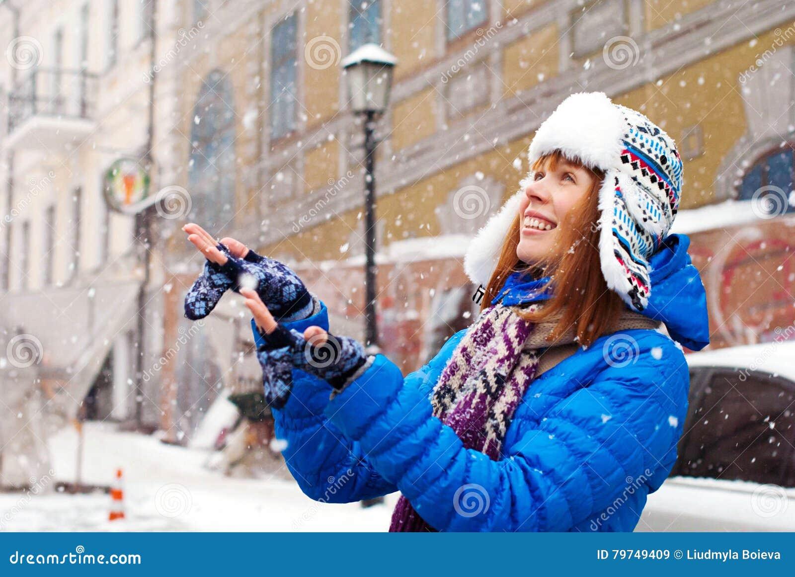 La muchacha elegante joven disfruta la primera nieve Nieve en la ciudad Dejáis le nevar Captura de la chica joven la nieve con su