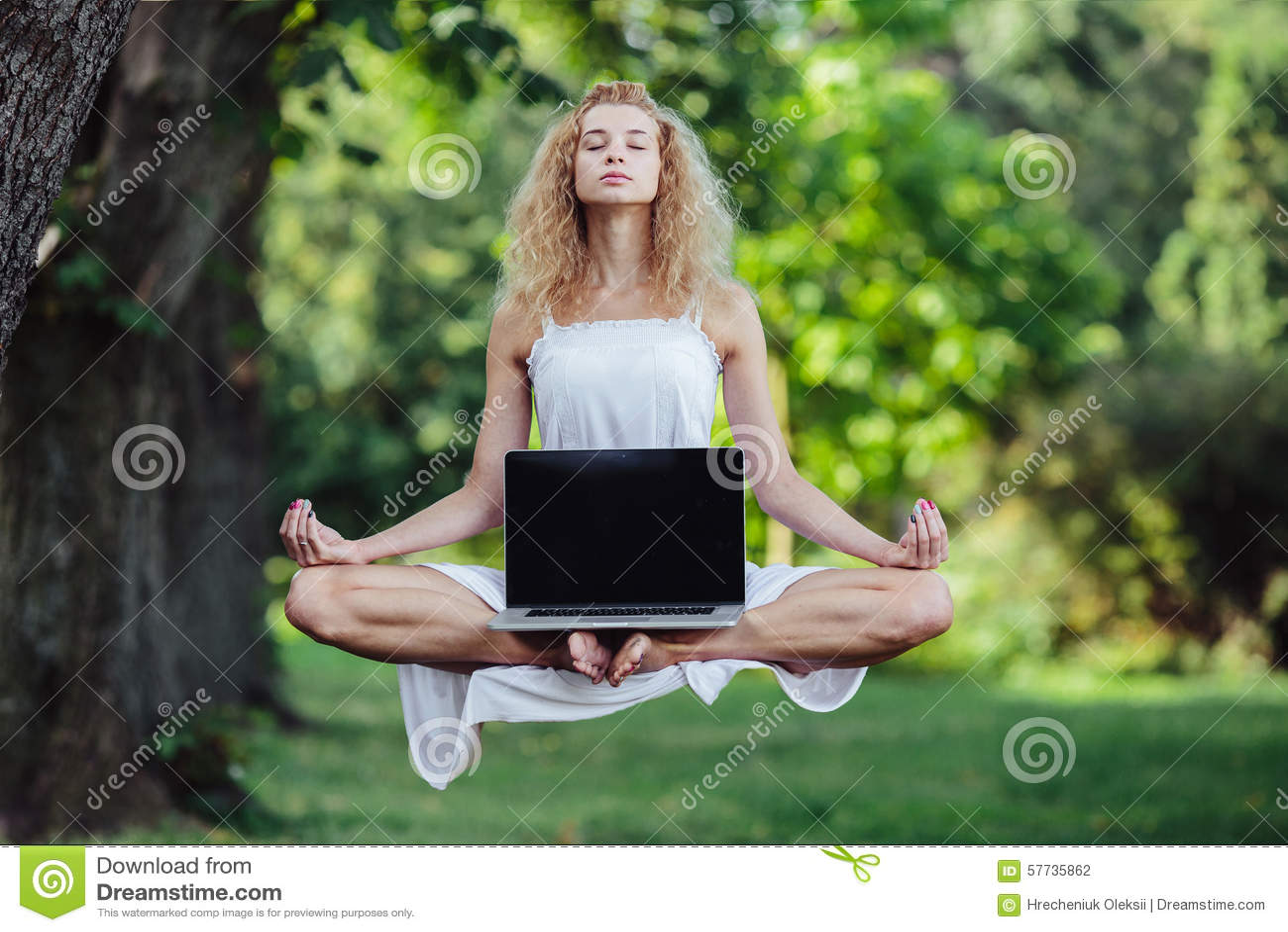 La muchacha eleva y mantiene flotando con el ordenador portátil