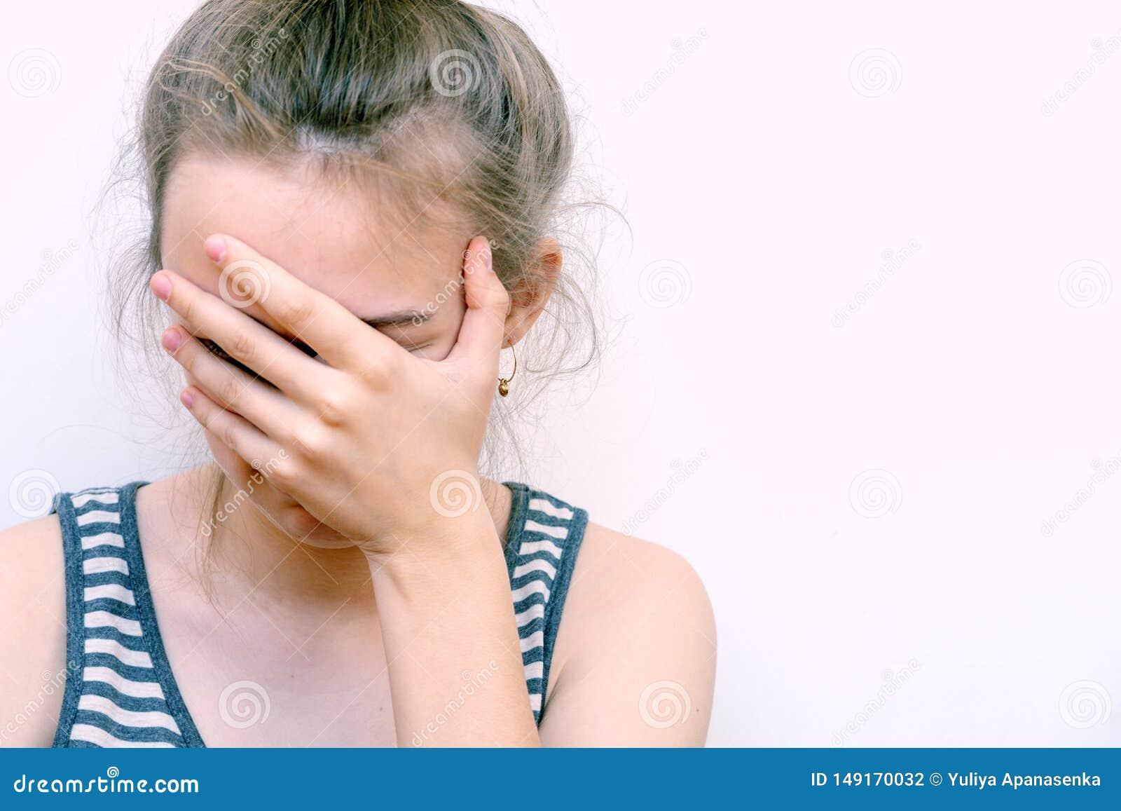 La muchacha en la desesperación cubre su cara con la mano Retrato subrayado de la hembra del dolor del dolor de cabeza de la muje