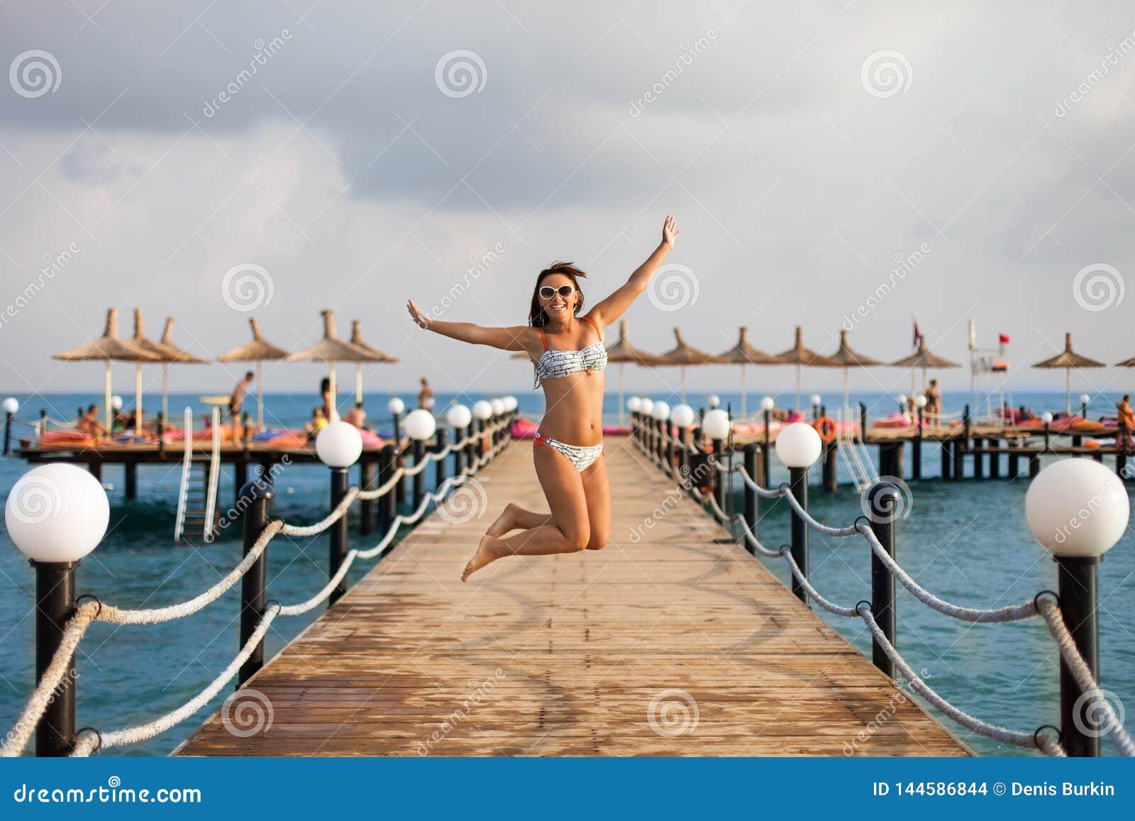 La muchacha en el traje de baño saltó en el embarcadero Muchacha feliz en el embarcadero Concepto de la libertad La muchacha enca