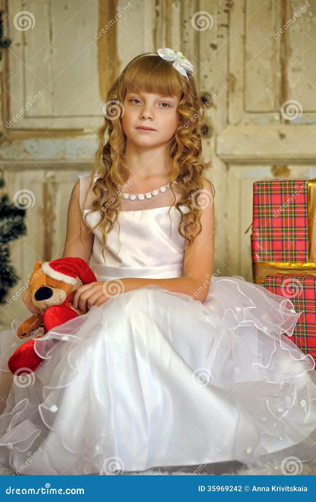La muchacha en el vestido blanco con un oso del juguete se sienta