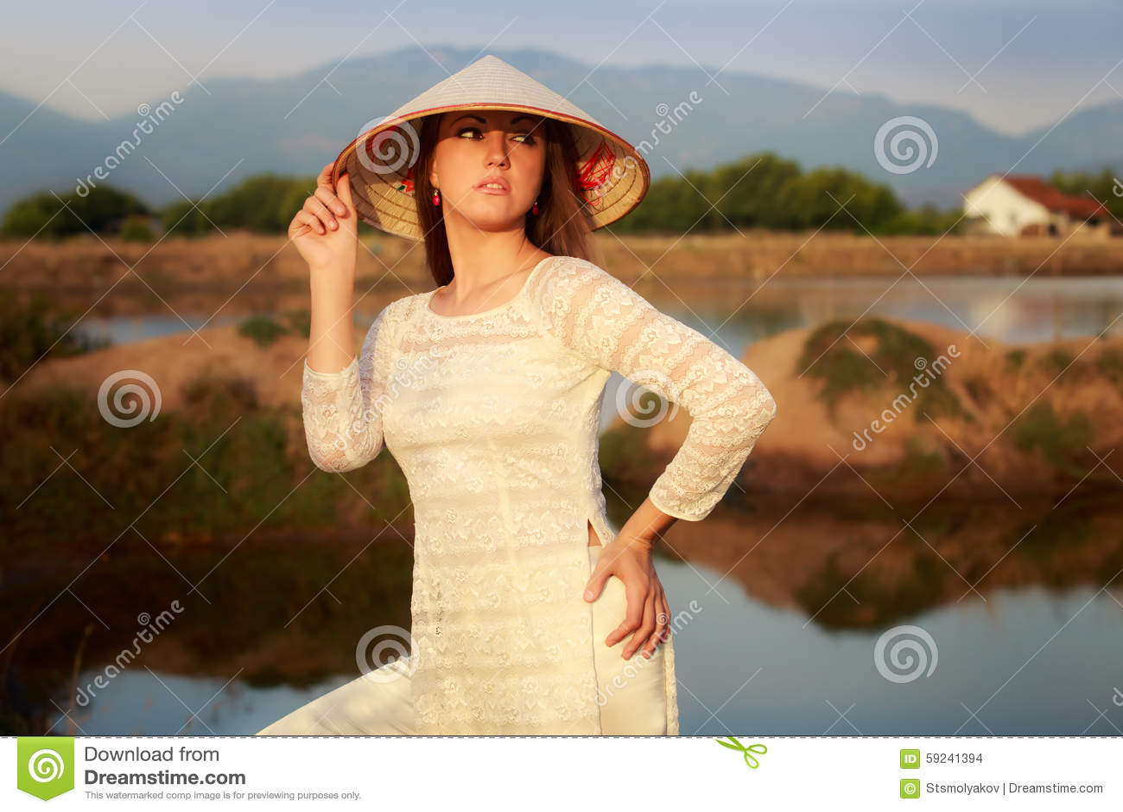 La muchacha en sombrero vietnamita contra los lagos oscila la reflexión