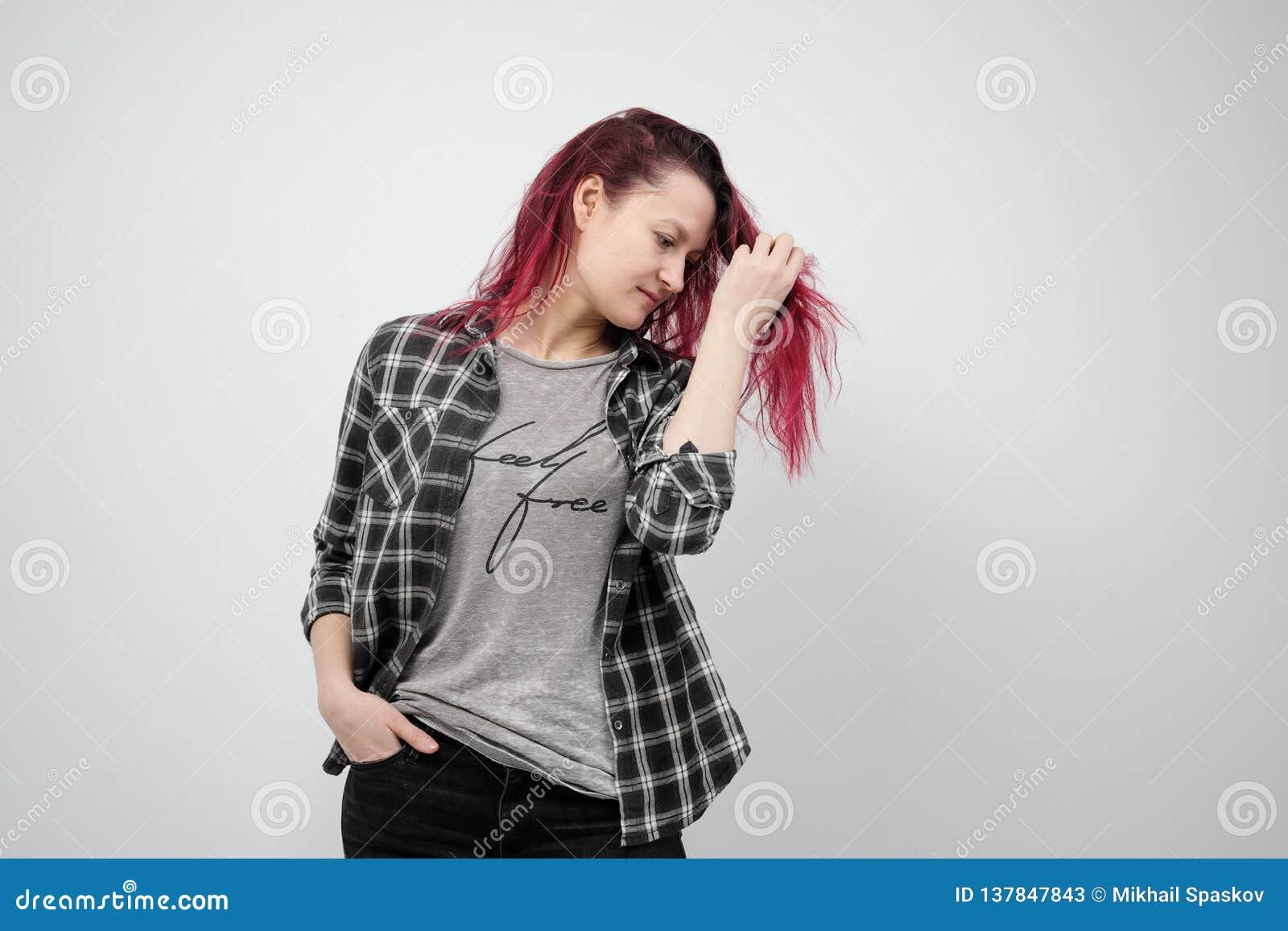 La muchacha en una camisa gris de la tela escocesa en un fondo blanco con el pelo rojo teñido
