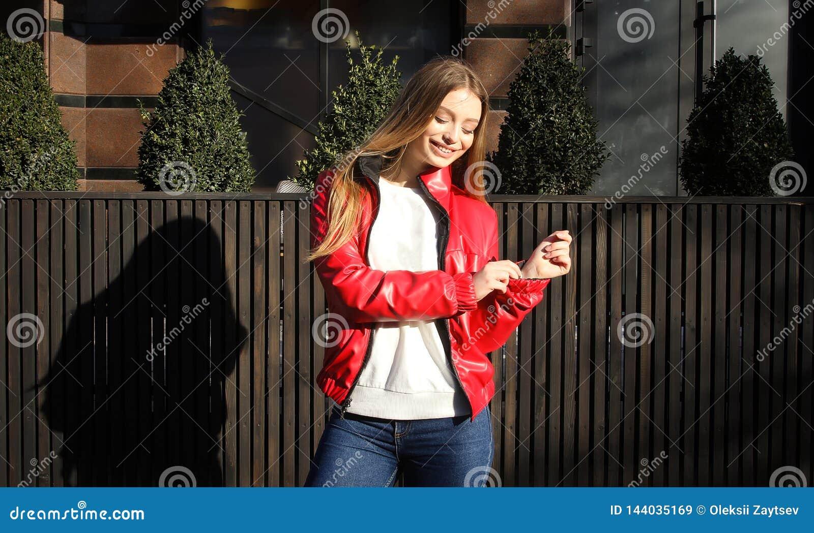 La muchacha en una chaqueta de la primavera se coloca cerca del café