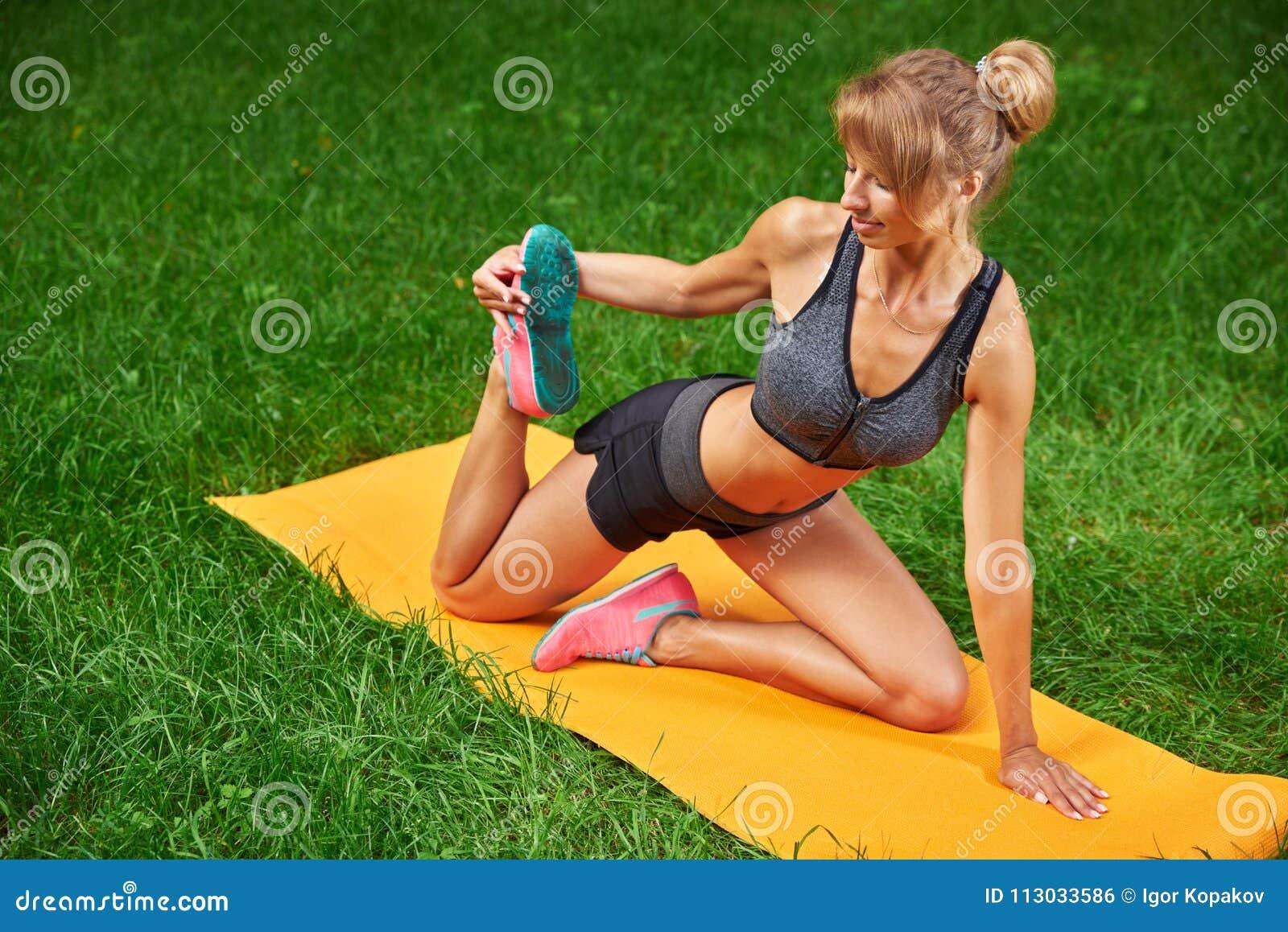 La muchacha enganchó en aptitud y gimnasia en el parque