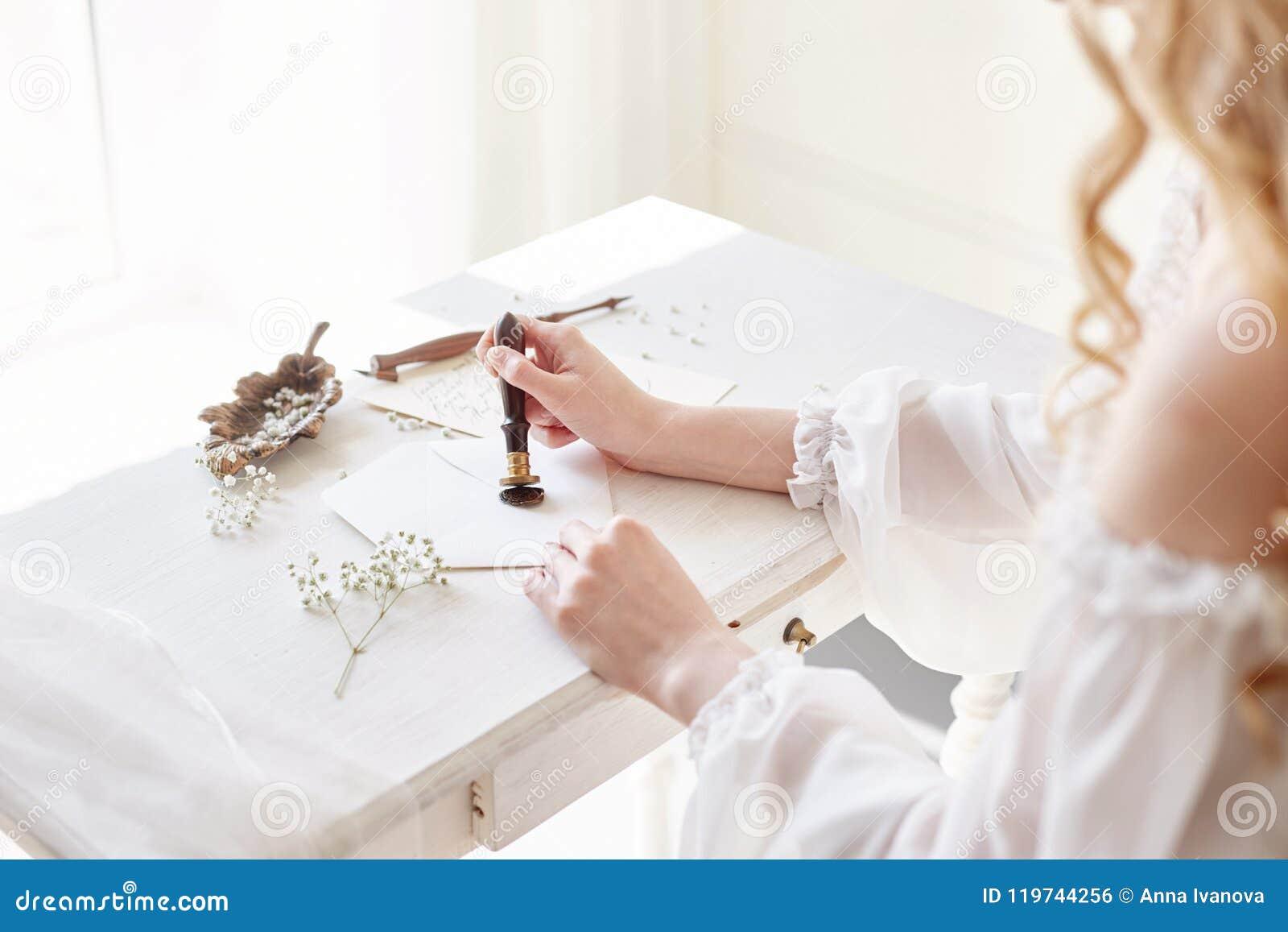 La muchacha escribe una letra a su hombre querido, sentándose en casa en la tabla en un vestido, una pureza y una inocencia de la