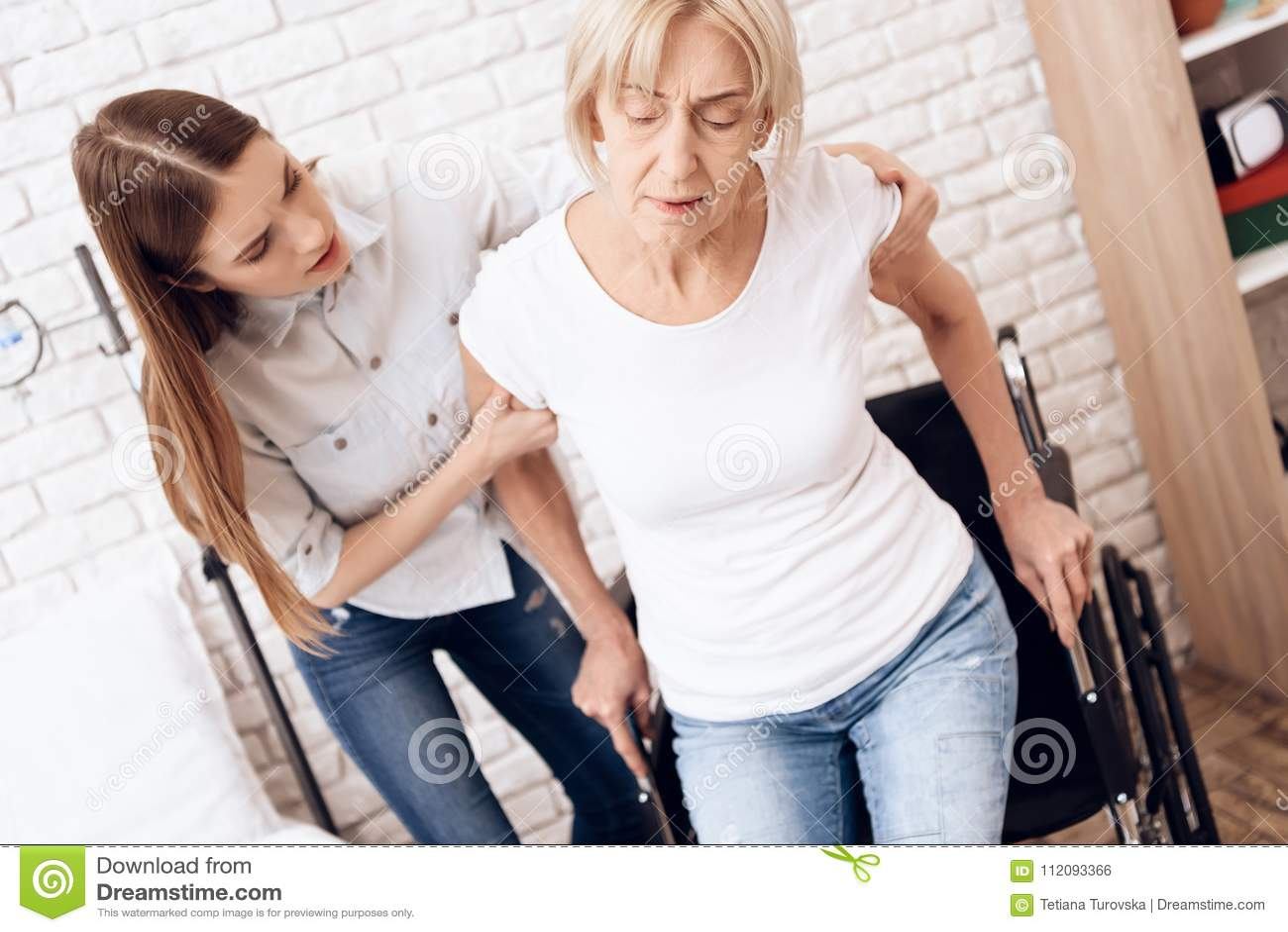 La muchacha está cuidando a la mujer mayor en casa La muchacha está ayudando a la mujer a conseguir en la silla de ruedas