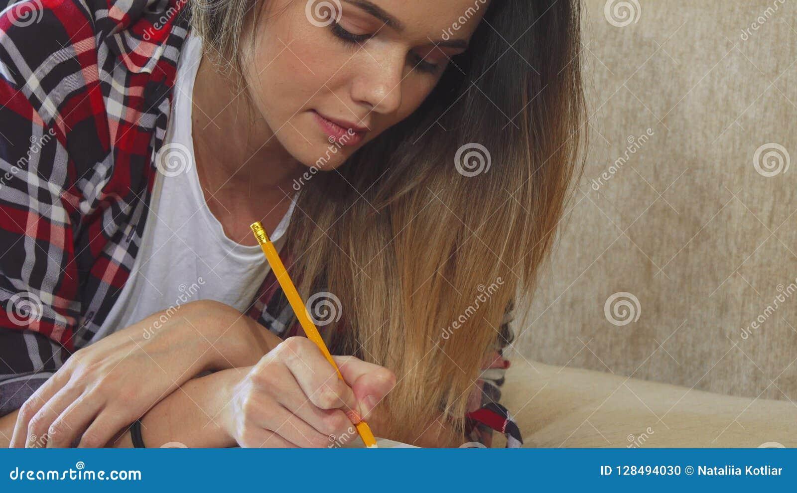La muchacha está escribiendo en su cuaderno
