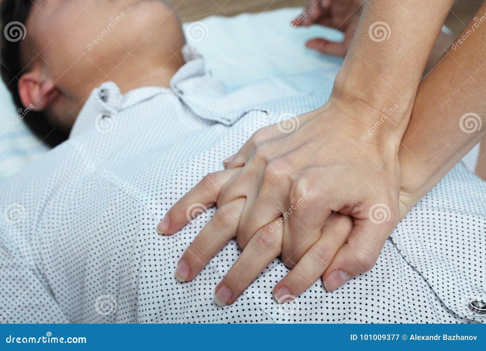 La muchacha está haciendo un masaje de corazón