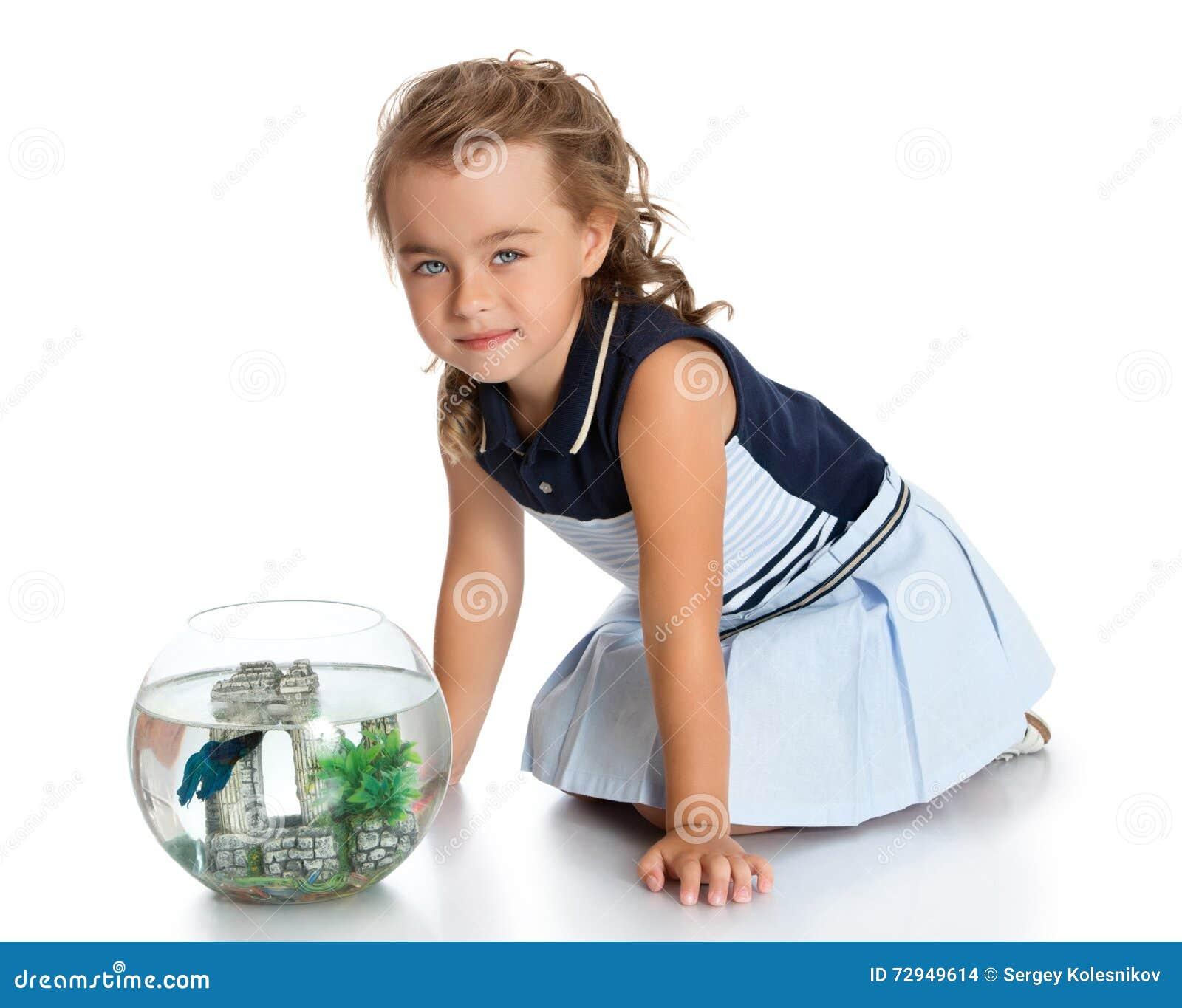 La muchacha está mirando pescados en un acuario