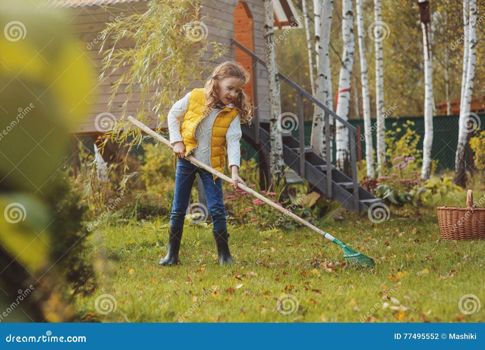 La muchacha feliz del niño que juega al pequeño jardinero en otoño y que escoge se va en cesta Trabajo estacional del jardín