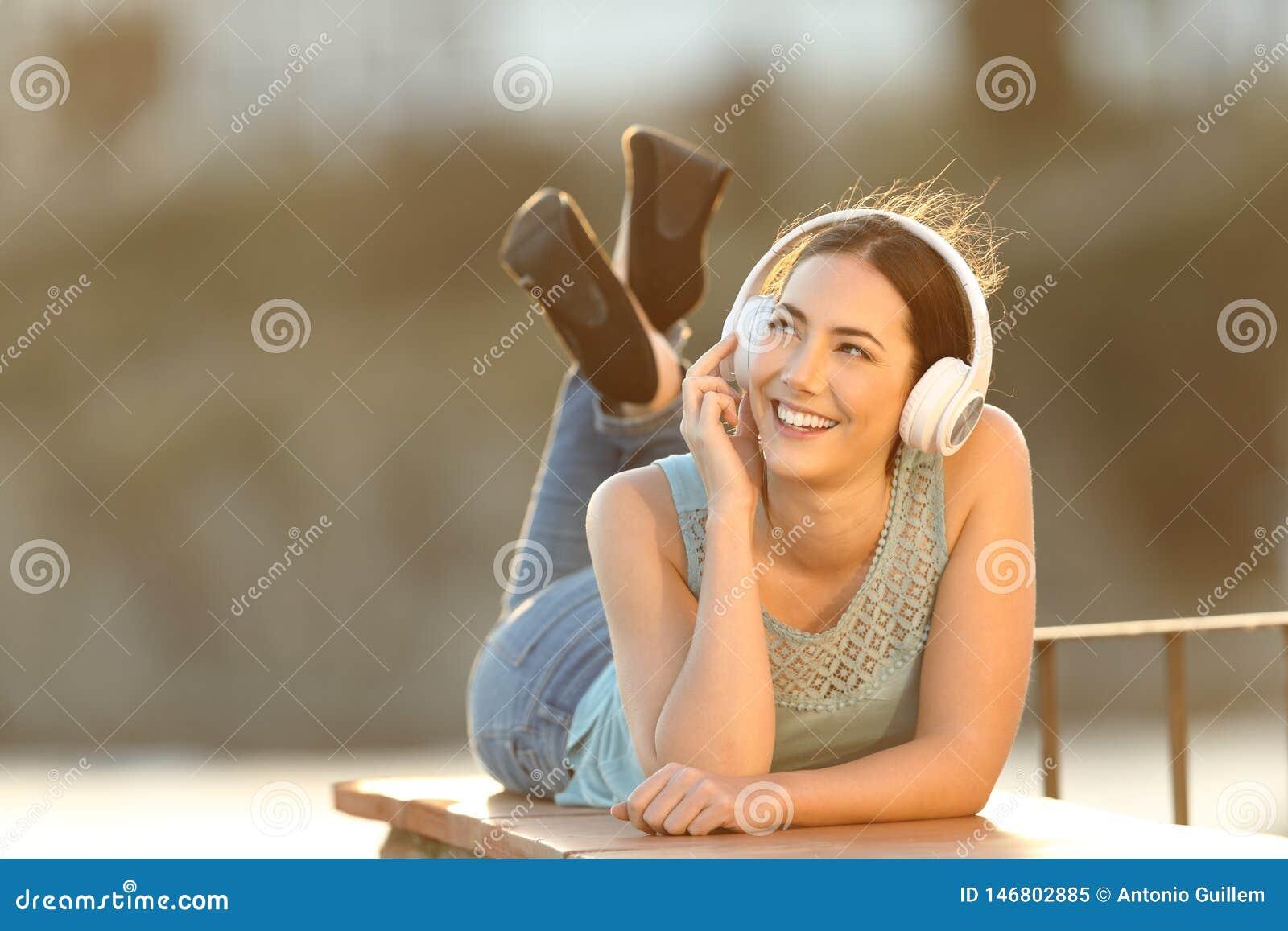 La muchacha feliz escucha la música que mira el lado