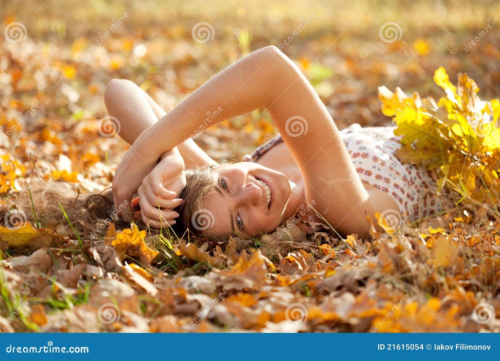 La muchacha feliz miente en parque del otoño