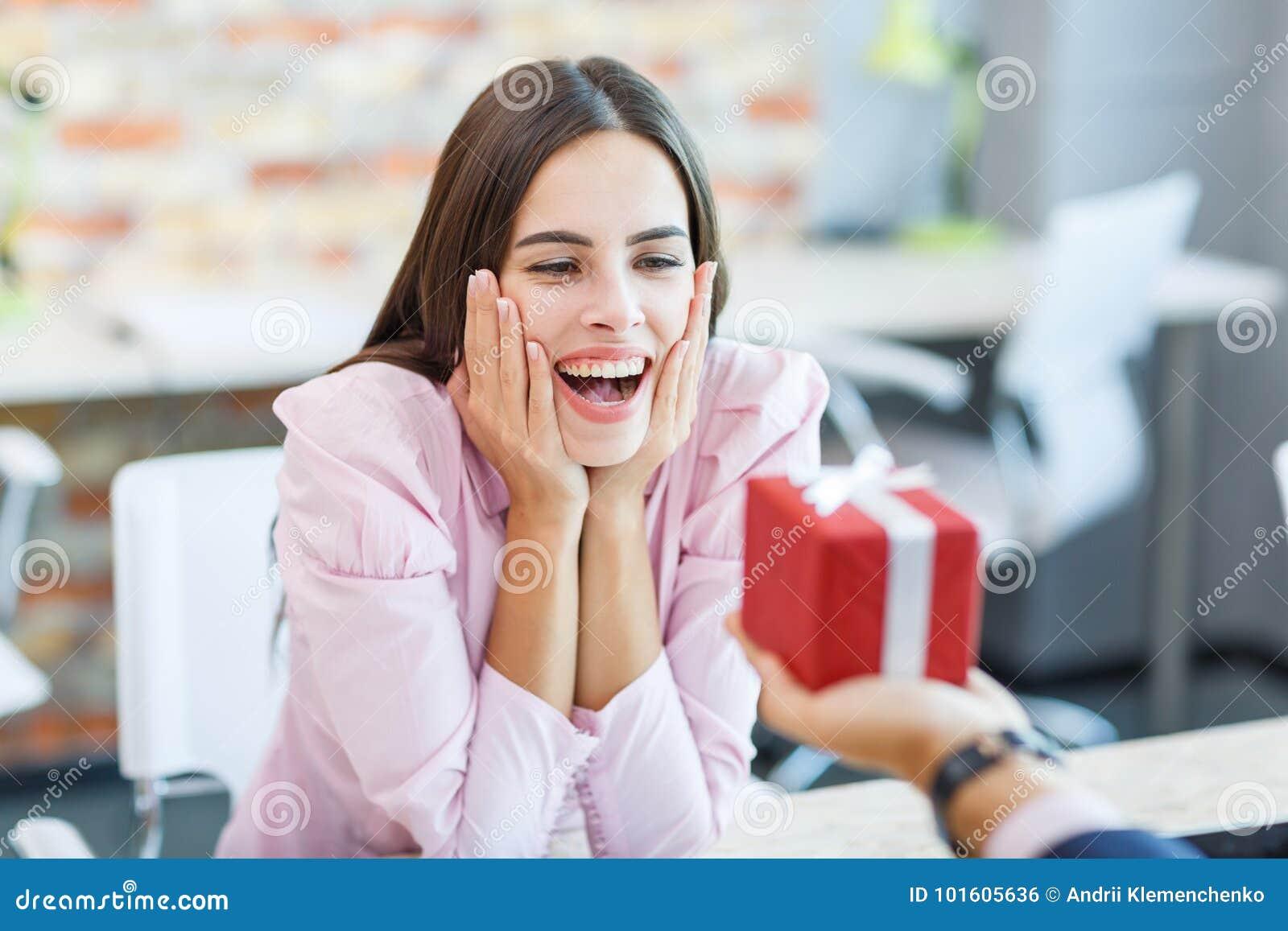 La muchacha feliz que trabajaba en la oficina recibió un regalo