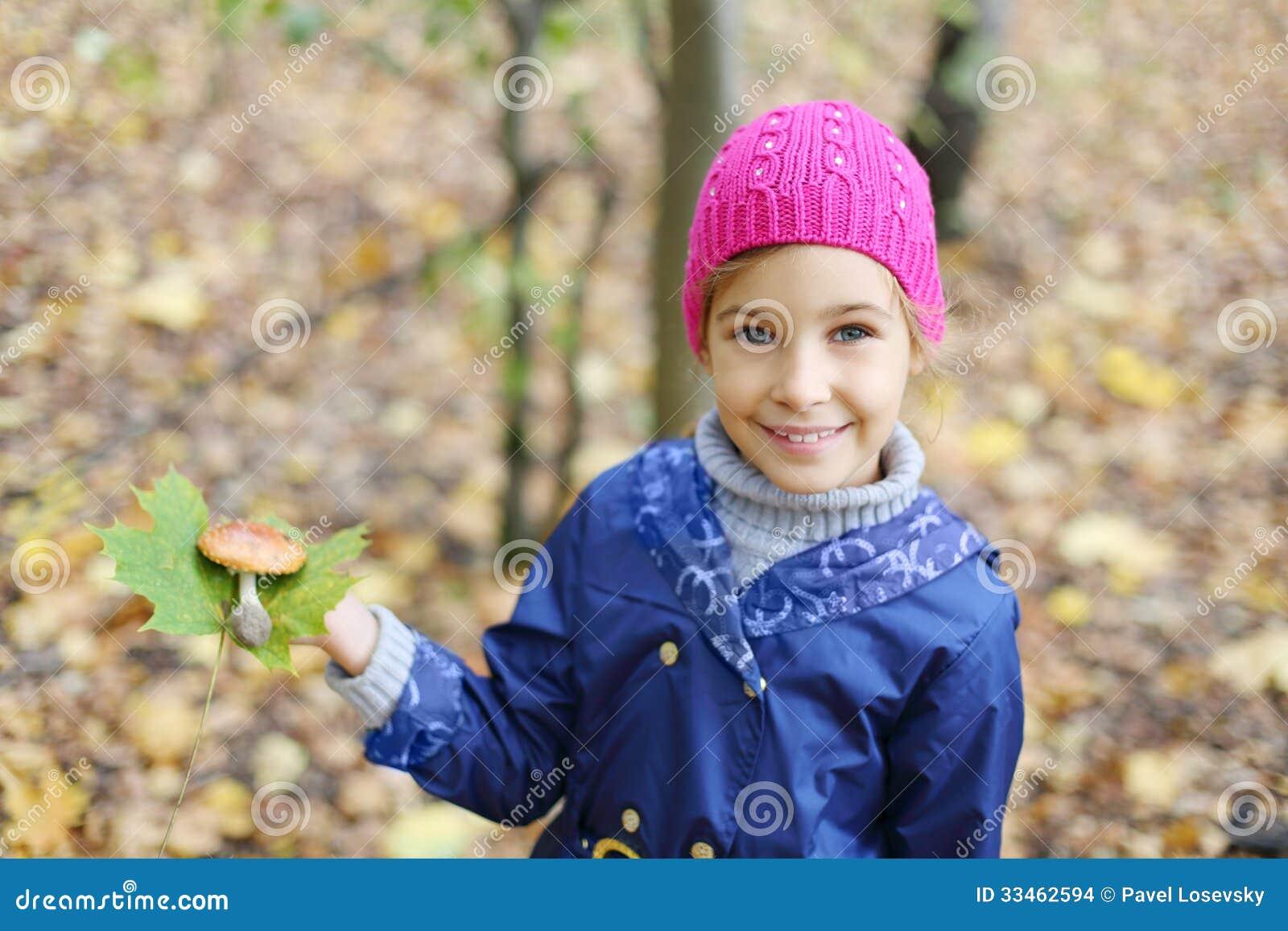 La muchacha feliz sostiene la hoja verde