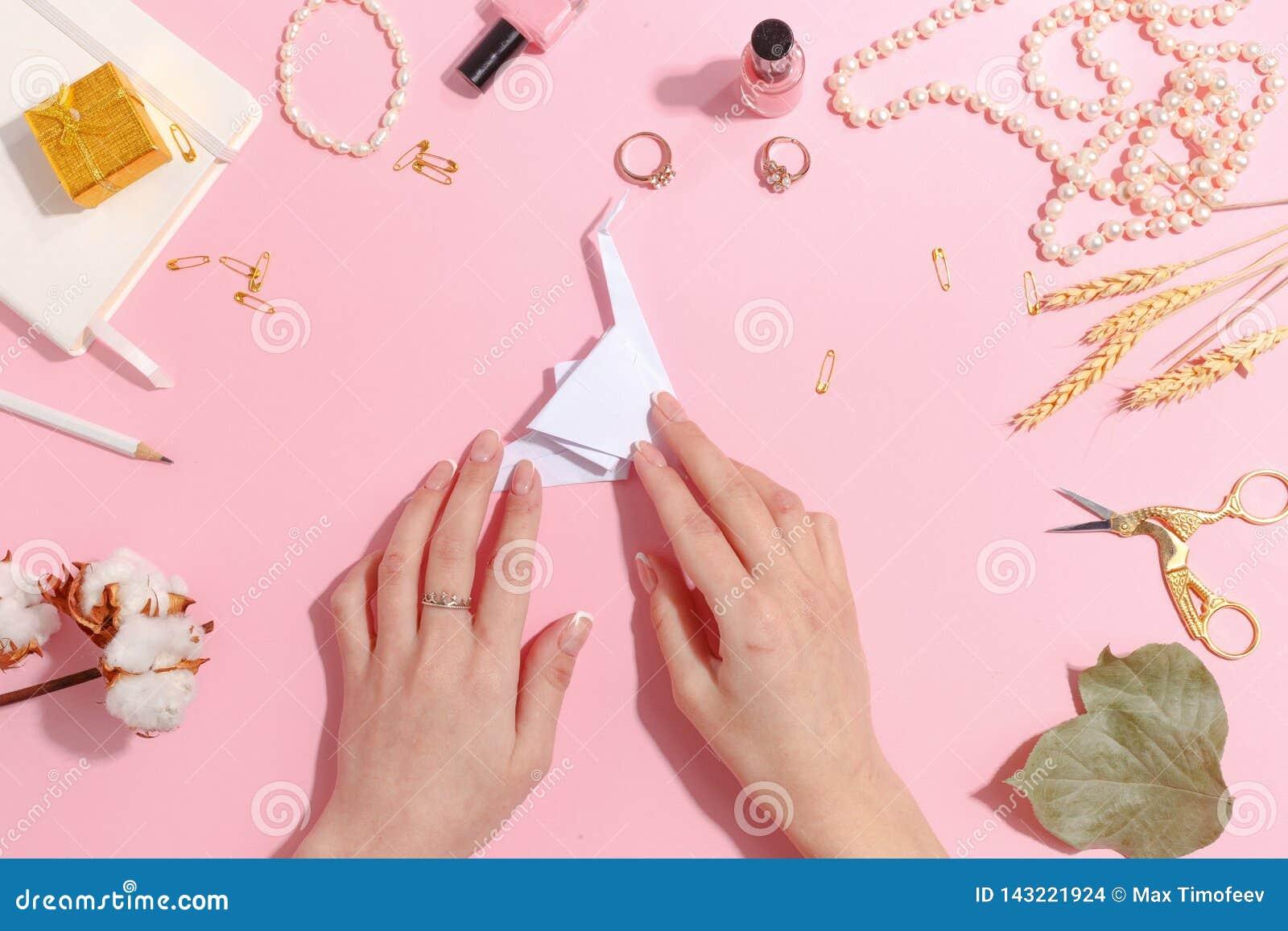 La muchacha hace la papiroflexia de papel de la grúa Visión superior