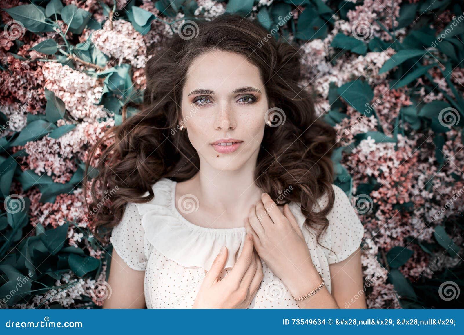 La muchacha hermosa adolescente que miente en lila florece el fondo Ascendente cercano del retrato