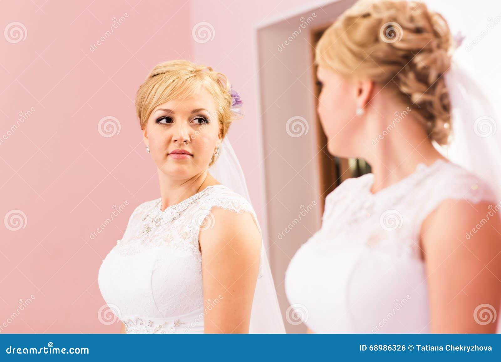 La muchacha hermosa de la novia con el peinado y el maquillaje brillante mira en el espejo