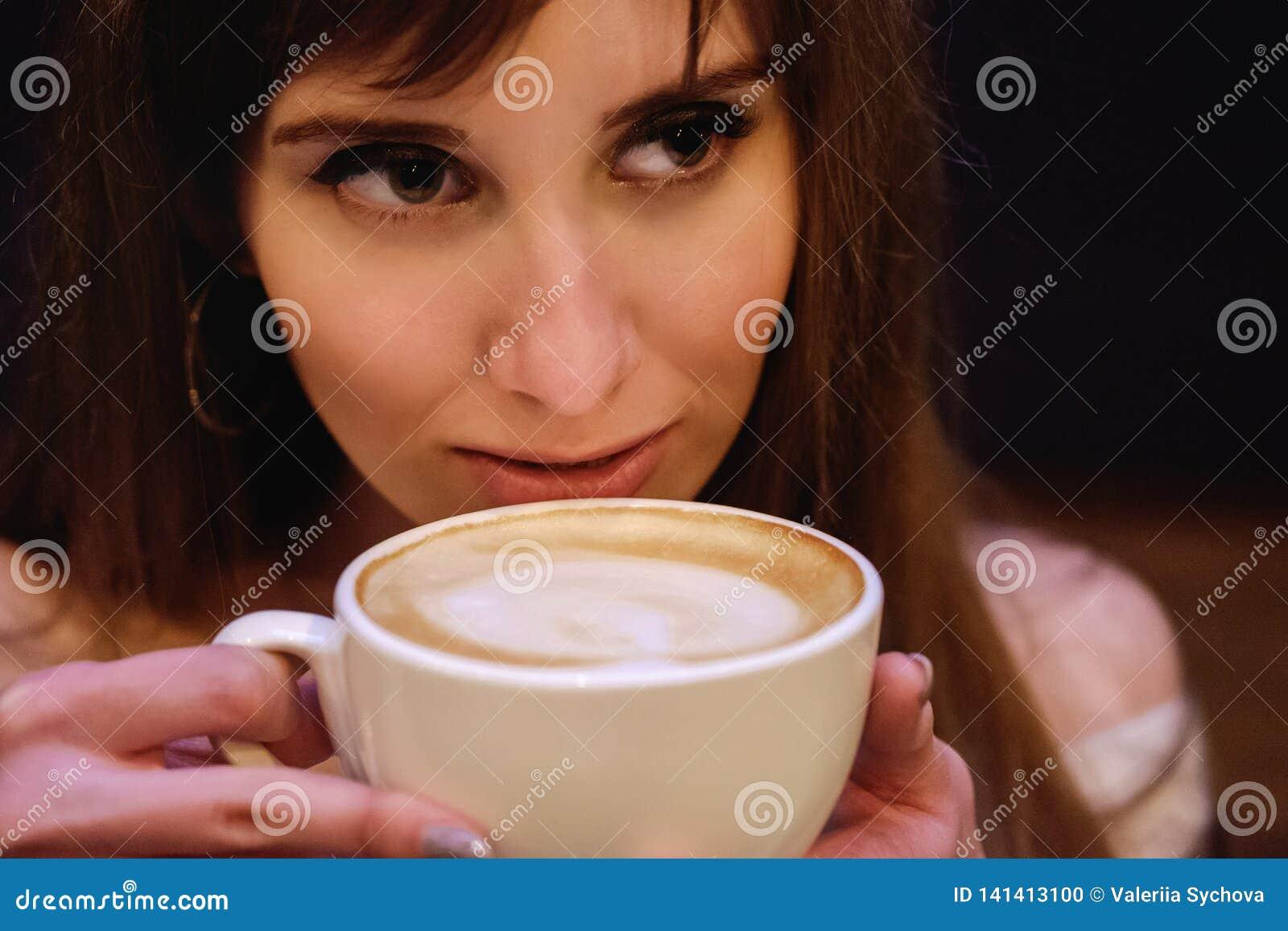 La muchacha hermosa de pelo largo en un suéter blanco se está colocando en una cafetería en una tabla de madera con una taza, ret