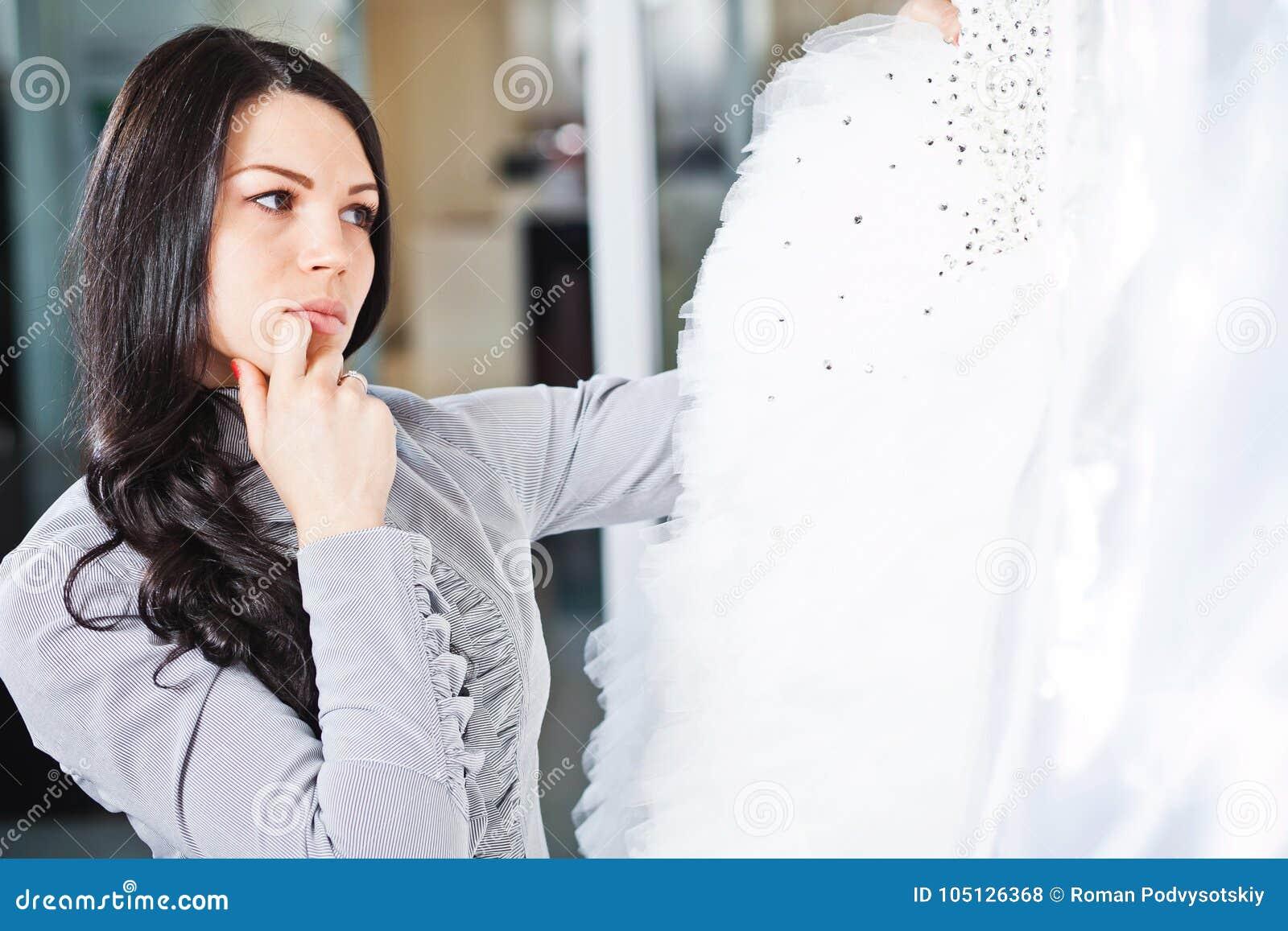 La muchacha hermosa elige su vestido de boda Retrato en el sa nupcial