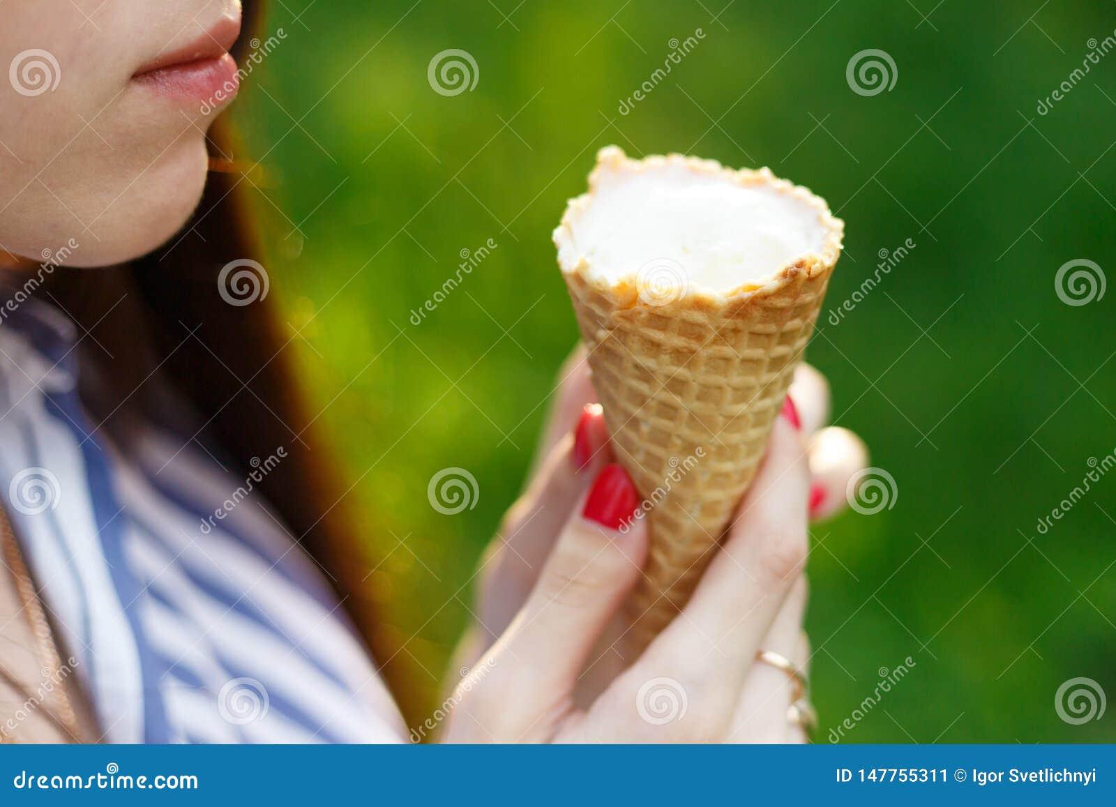 La muchacha hermosa joven con el pelo que fluye largo come el helado