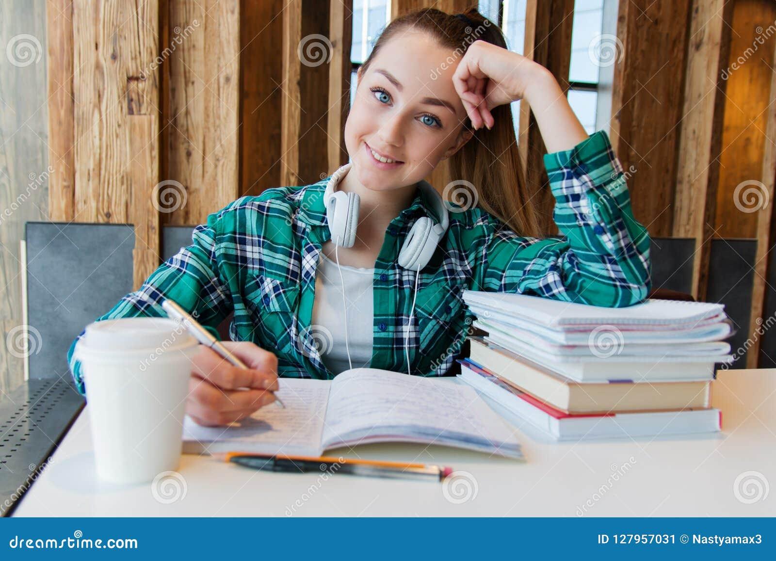 La muchacha hermosa joven del estudiante está haciendo su preparación o se está preparando a los exámenes que localizan con los c