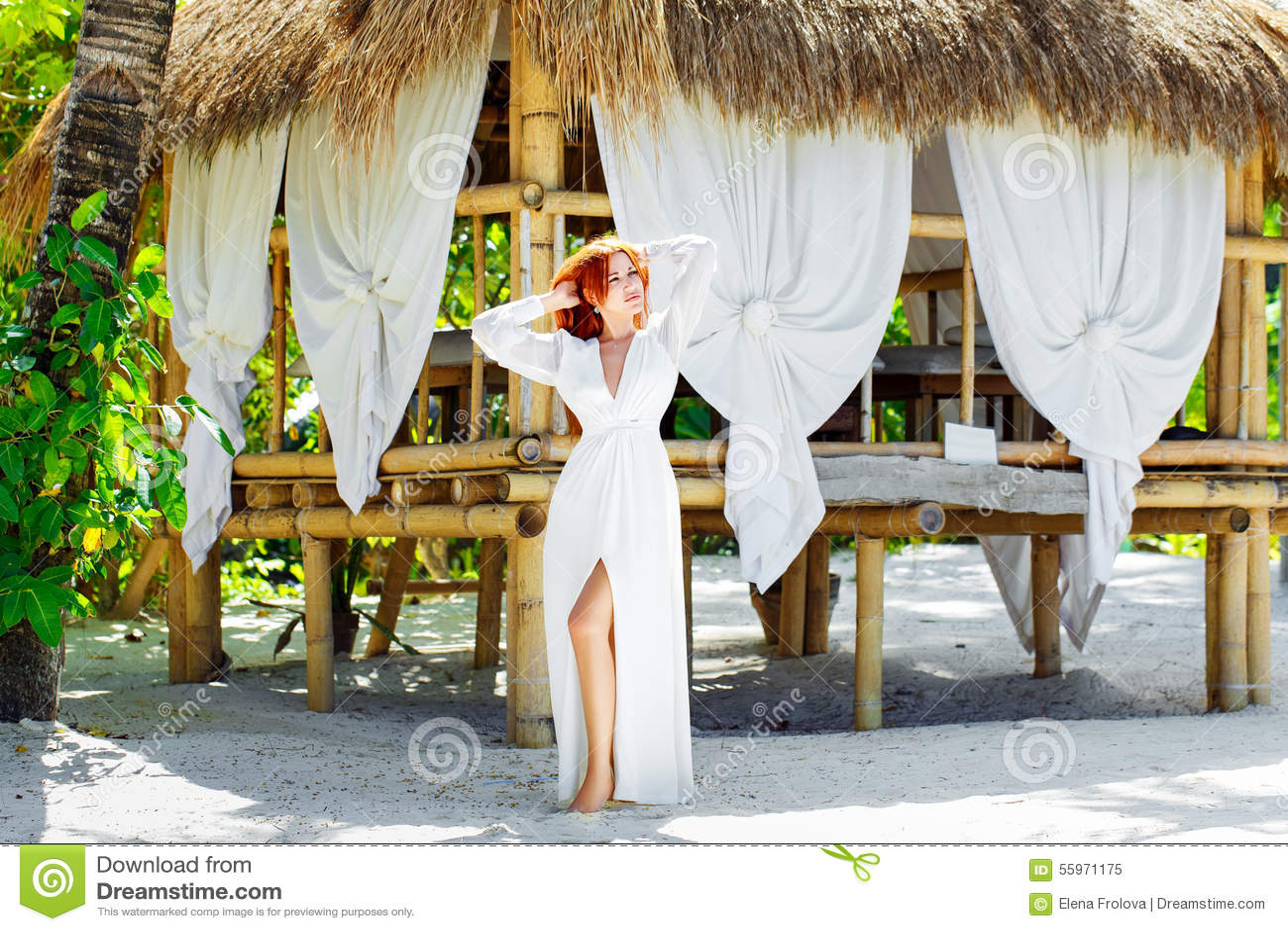 La muchacha hermosa joven en el vestido blanco coloca después una choza de bambú encendido