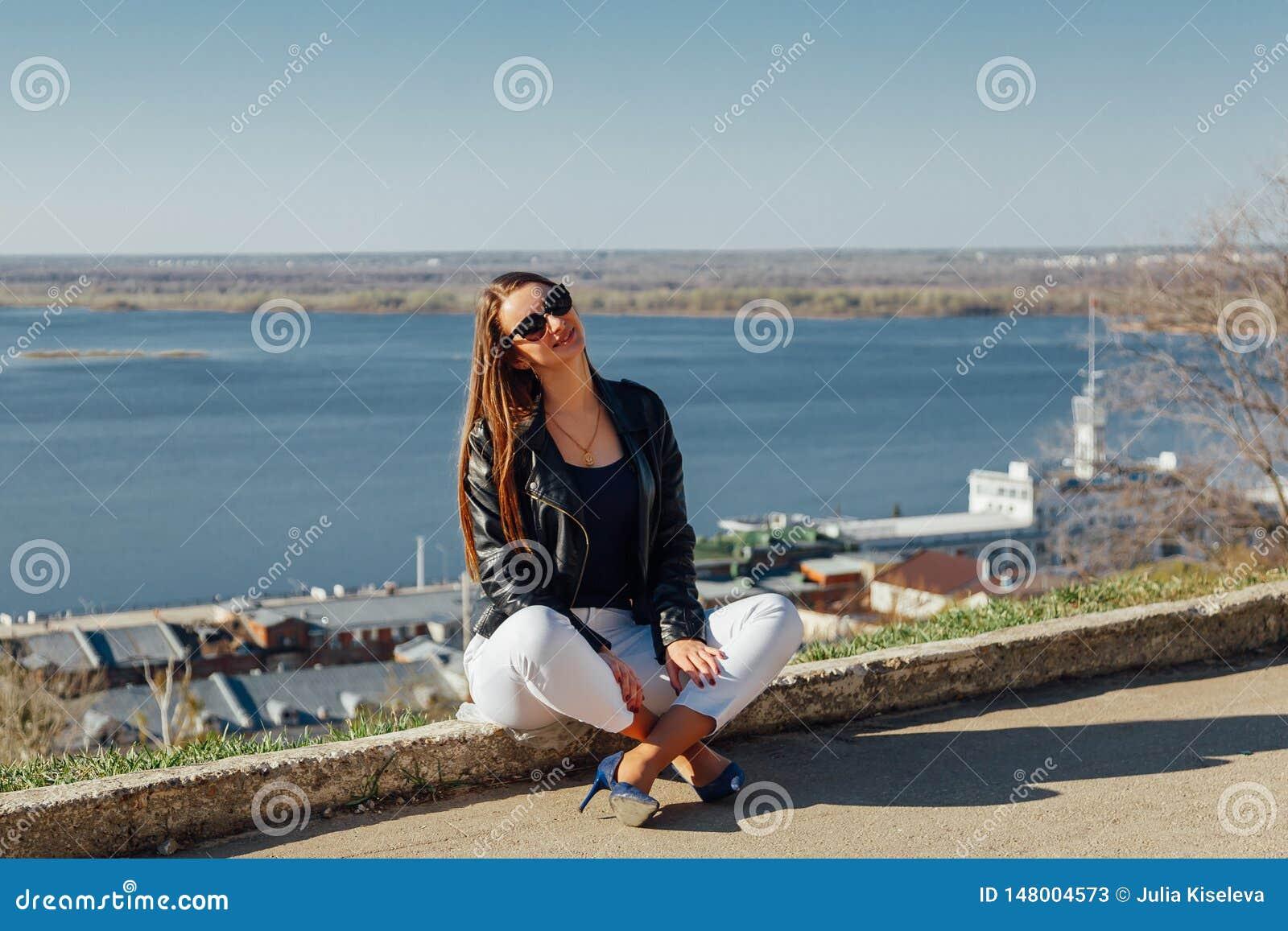 La muchacha hermosa joven se sienta en un parapeto del ladrillo
