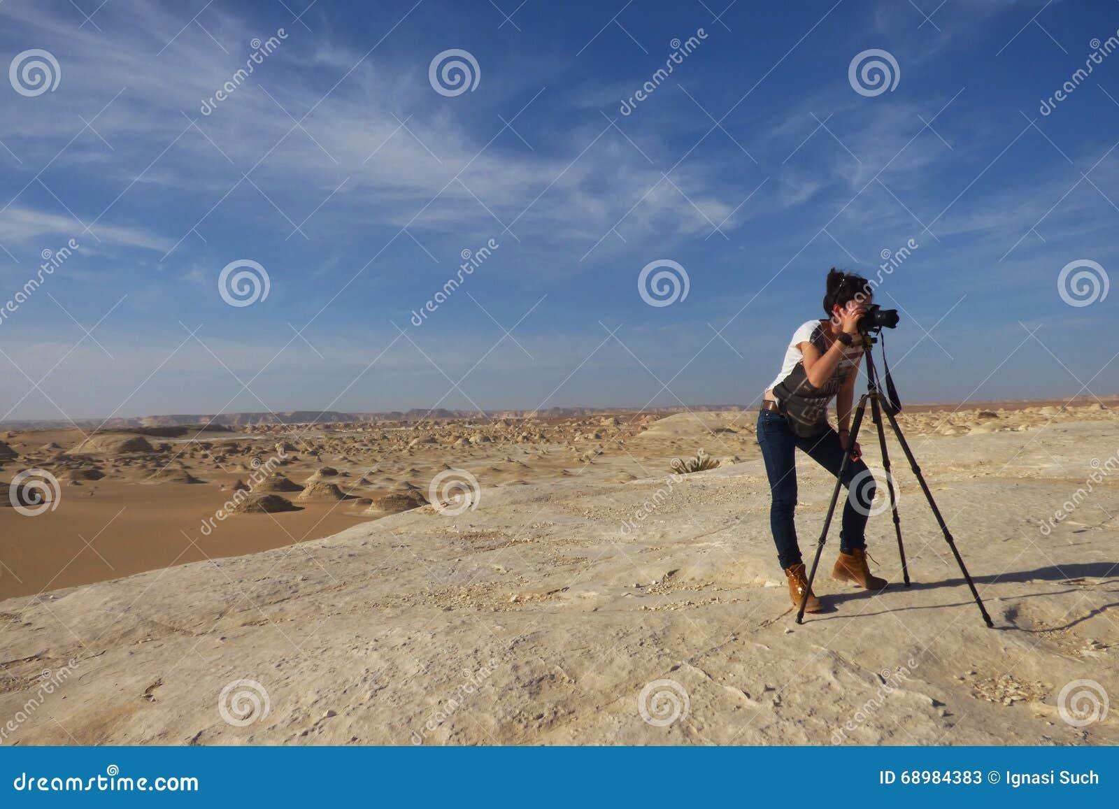 La muchacha hermosa joven toma una imagen en el medio del desierto blanco asombroso cerca del oasis de Farafra en Egipto