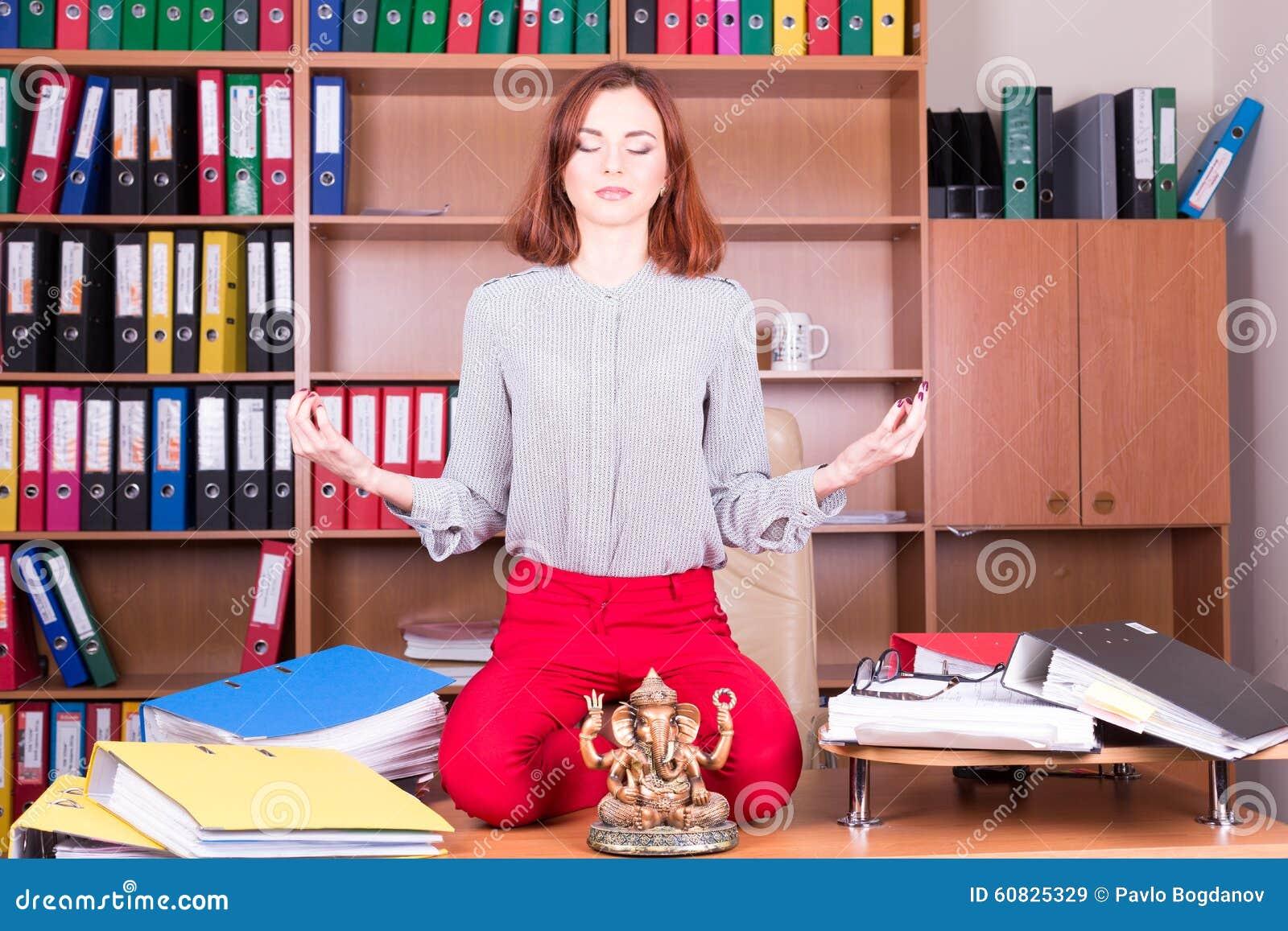La muchacha hermosa medita en oficina