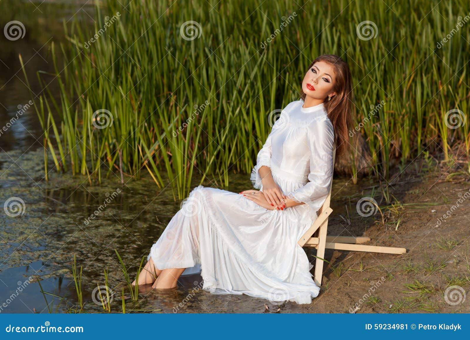 Download La Muchacha Hermosa Se Sienta En La Orilla Del Lago Imagen de archivo - Imagen de equanimity, vacaciones: 59234981
