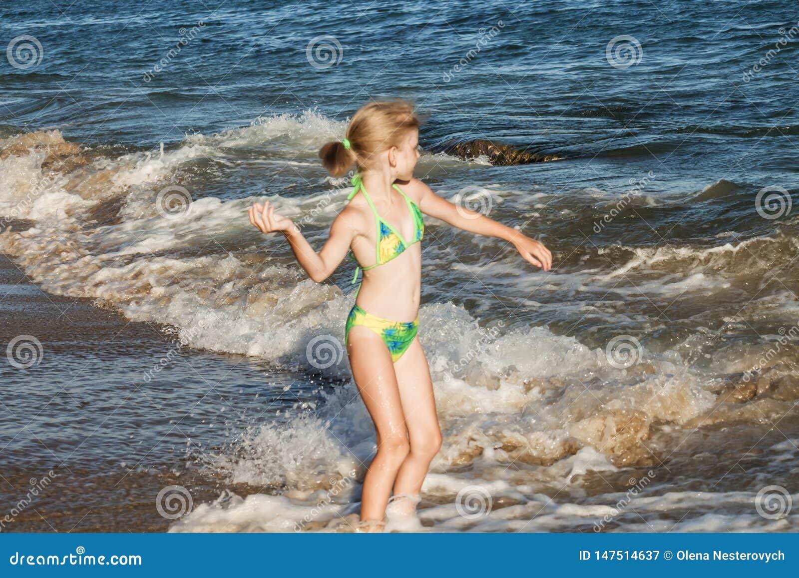 La muchacha hermosa y feliz en un traje de baño verde lanza un guijarro en el mar, concepto de la playa