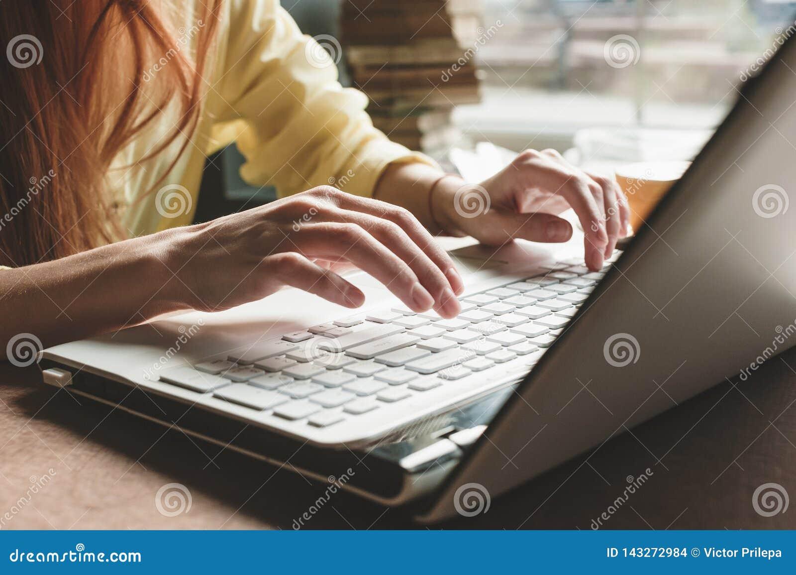 La muchacha imprime en un ordenador blanco Primer de manos en el teclado de un ordenador