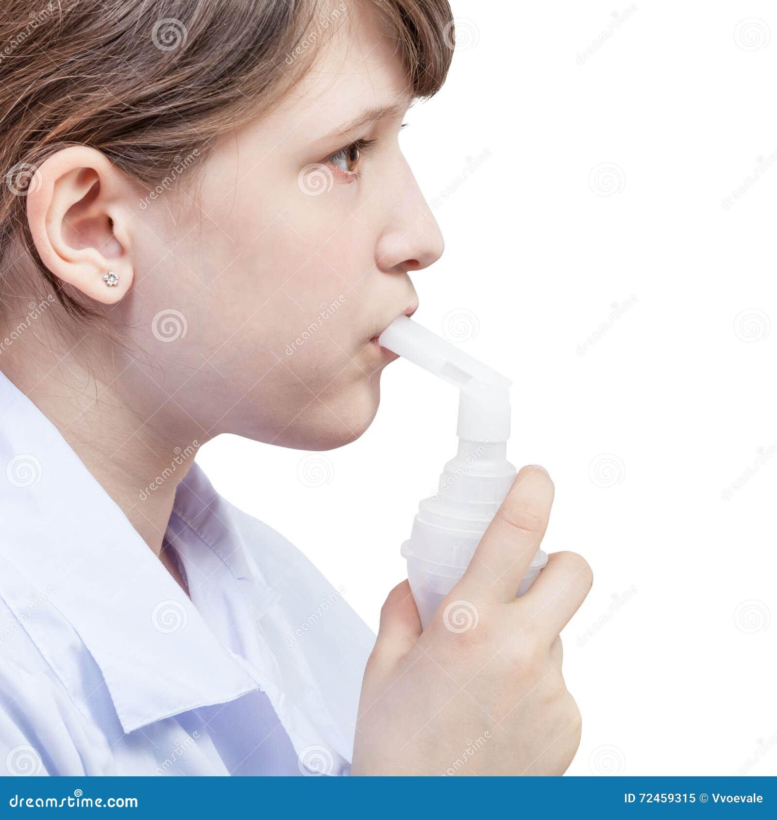 La muchacha inhala con la boquilla del nebulizador del jet
