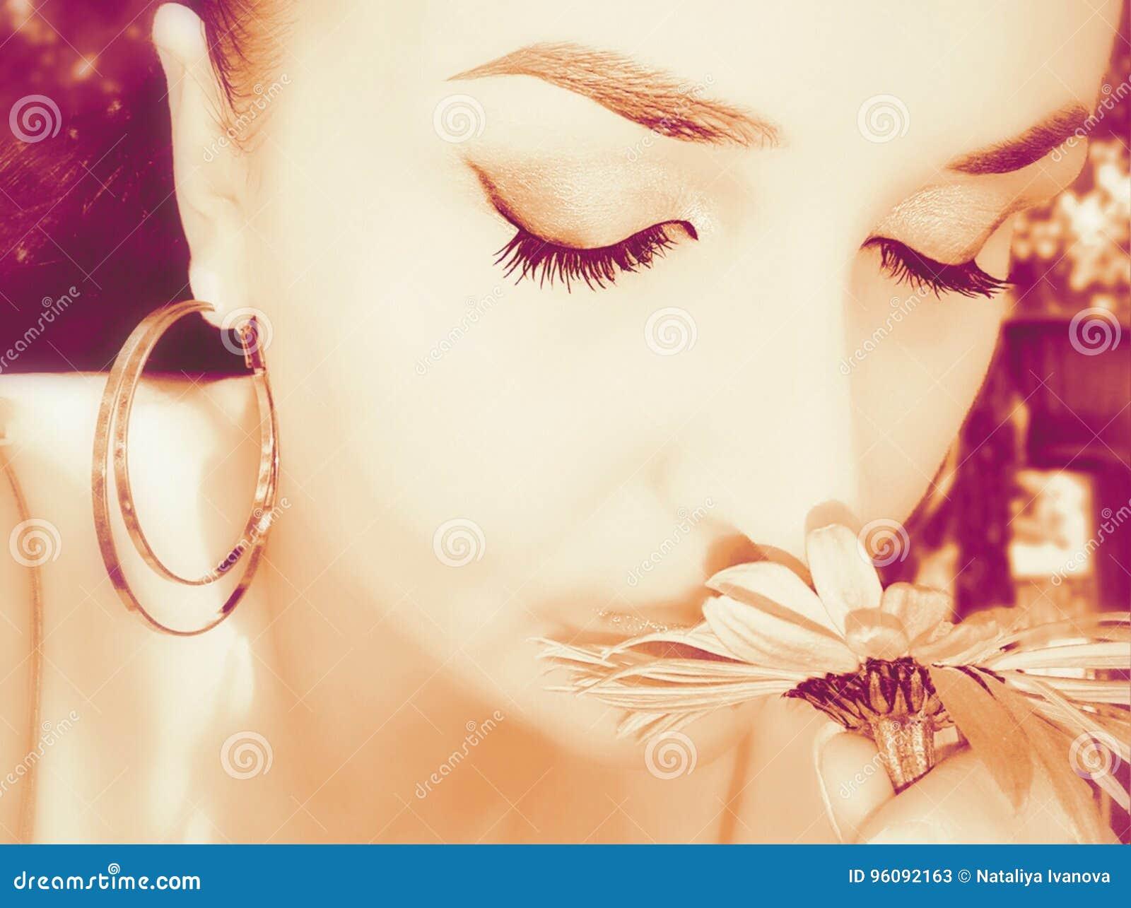 La muchacha inhala la fragancia de flores