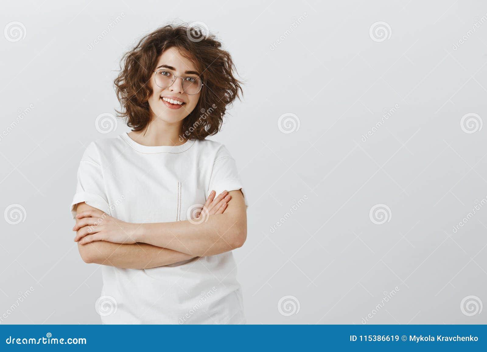 La muchacha le gusta trabajar en equipo Compañero de trabajo amistoso alegre en vidrios de moda con el pelo rizado corto, llevand
