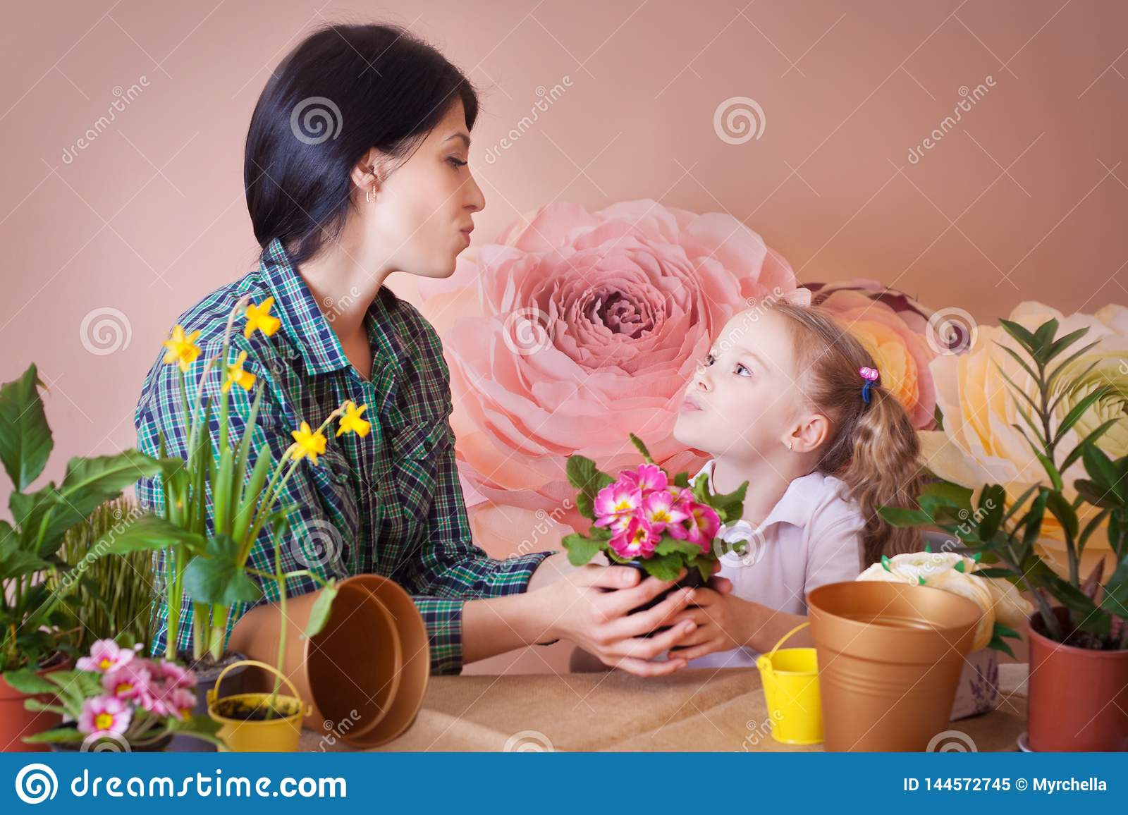 La muchacha linda del ni?o ayuda a su madre a cuidar para las plantas