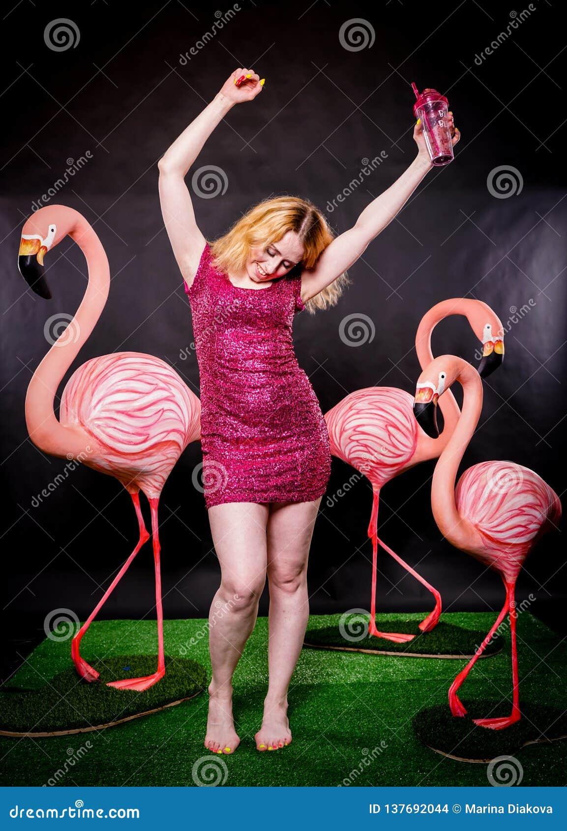 La muchacha linda en lentejuelas fucsias viste la reclinación y el baile con tres flamencos grandes en fondo negro