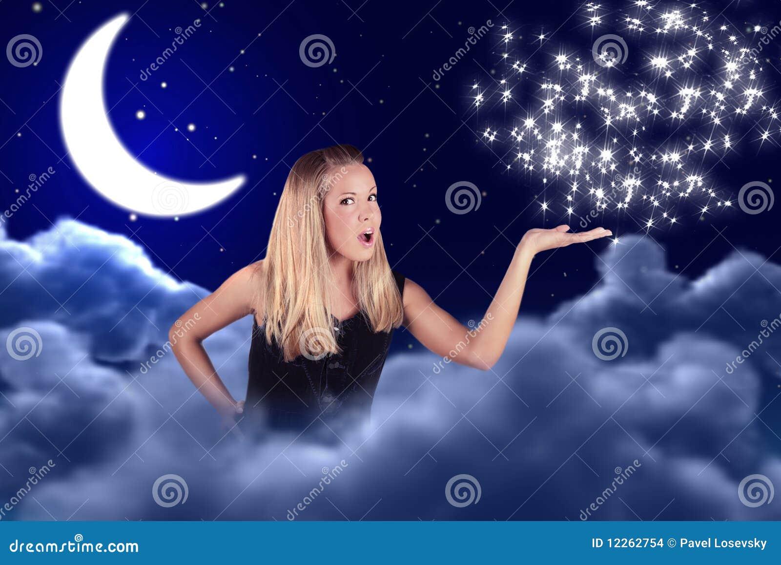La muchacha lleva a cabo algo en la mano en cielo con la luna