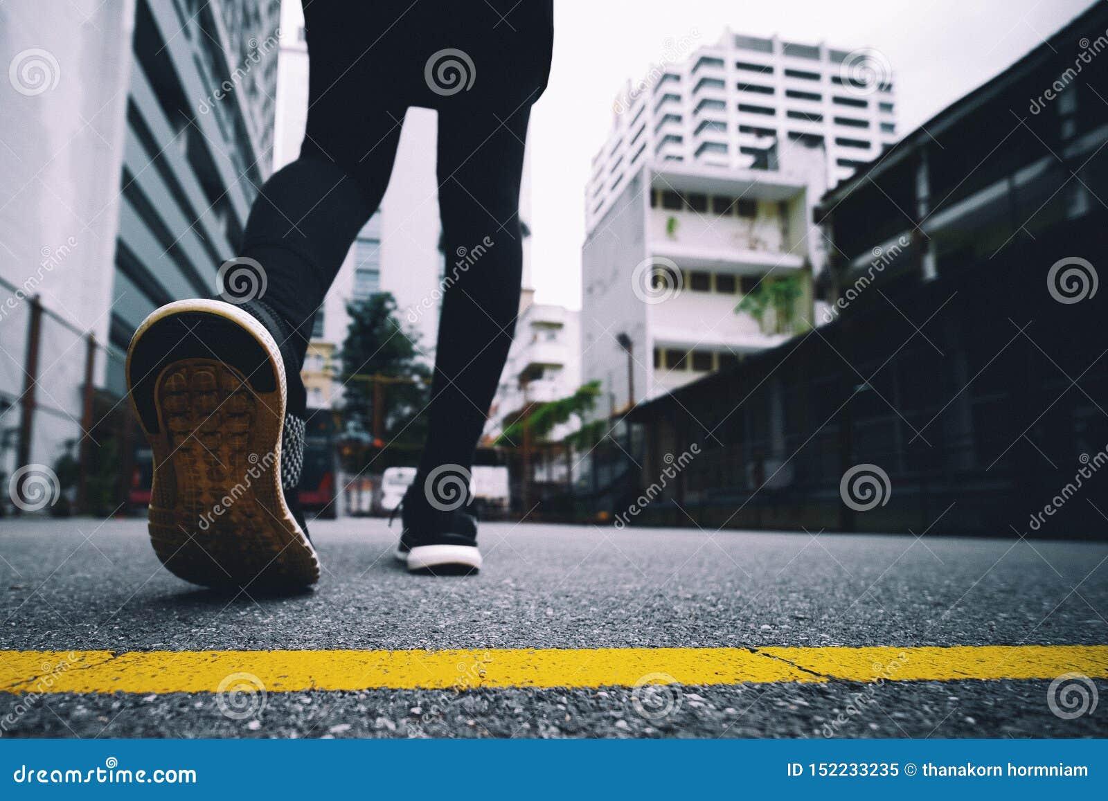 La muchacha lleva las zapatillas deportivas negras para correr en el parque