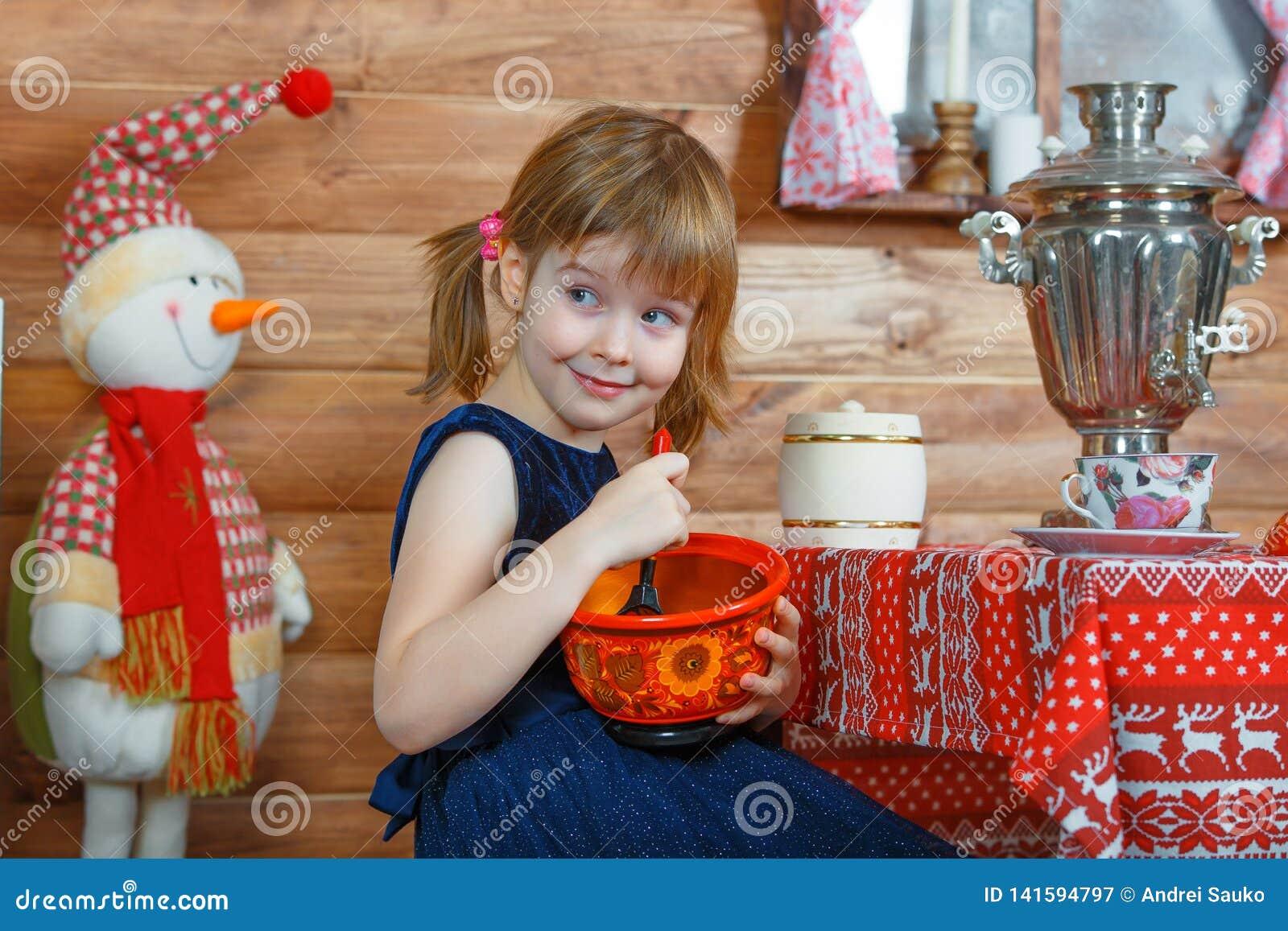 La muchacha Masha cocina las gachas de avena