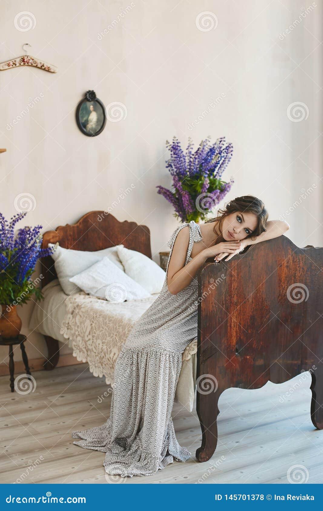 La muchacha modelo morena hermosa con los labios llenos atractivos en el vestido elegante se sienta en la cama del vintage en el