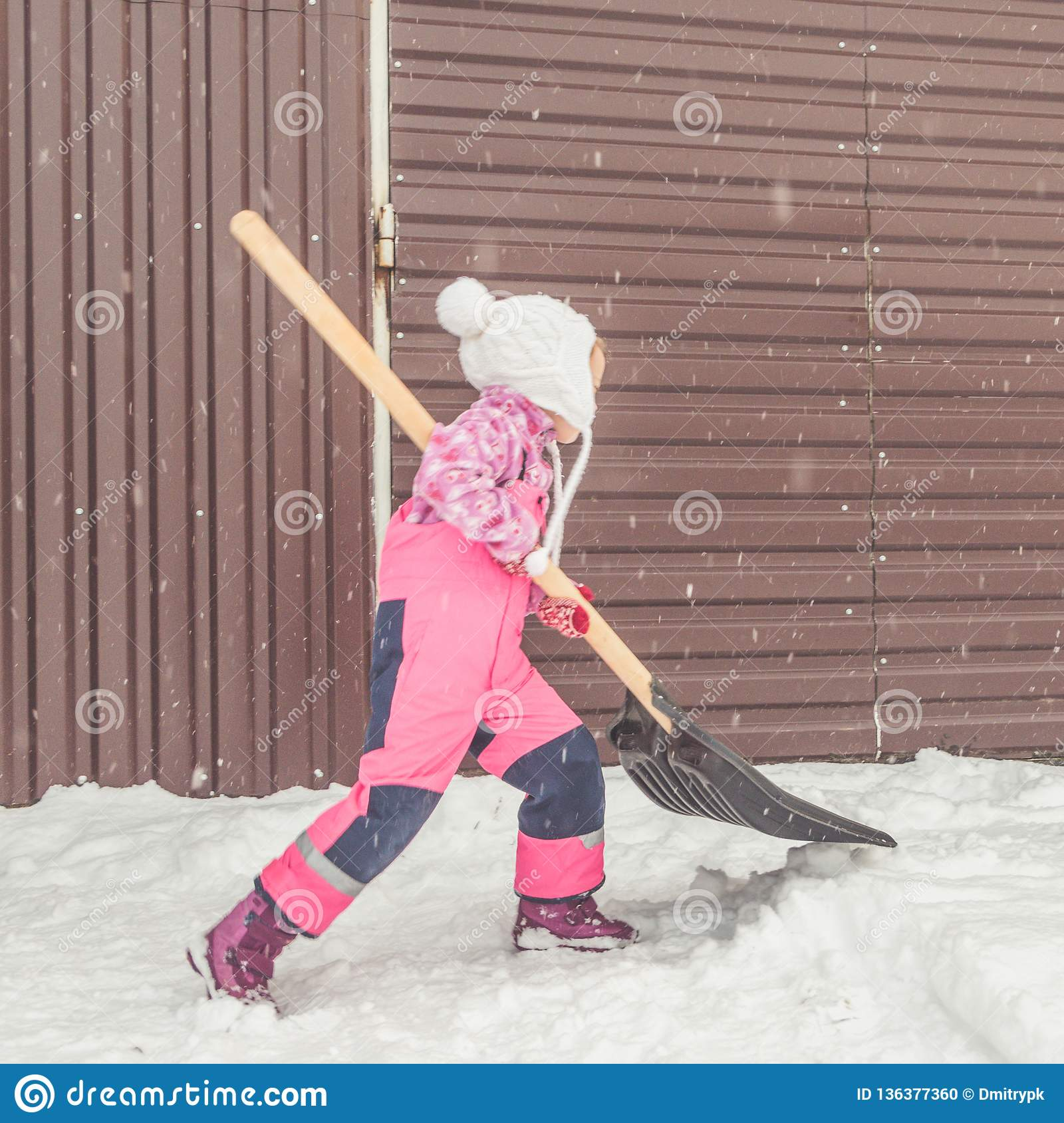 La muchacha, pala grande del bebé quita nieve de la trayectoria en el patio trasero en el garaje
