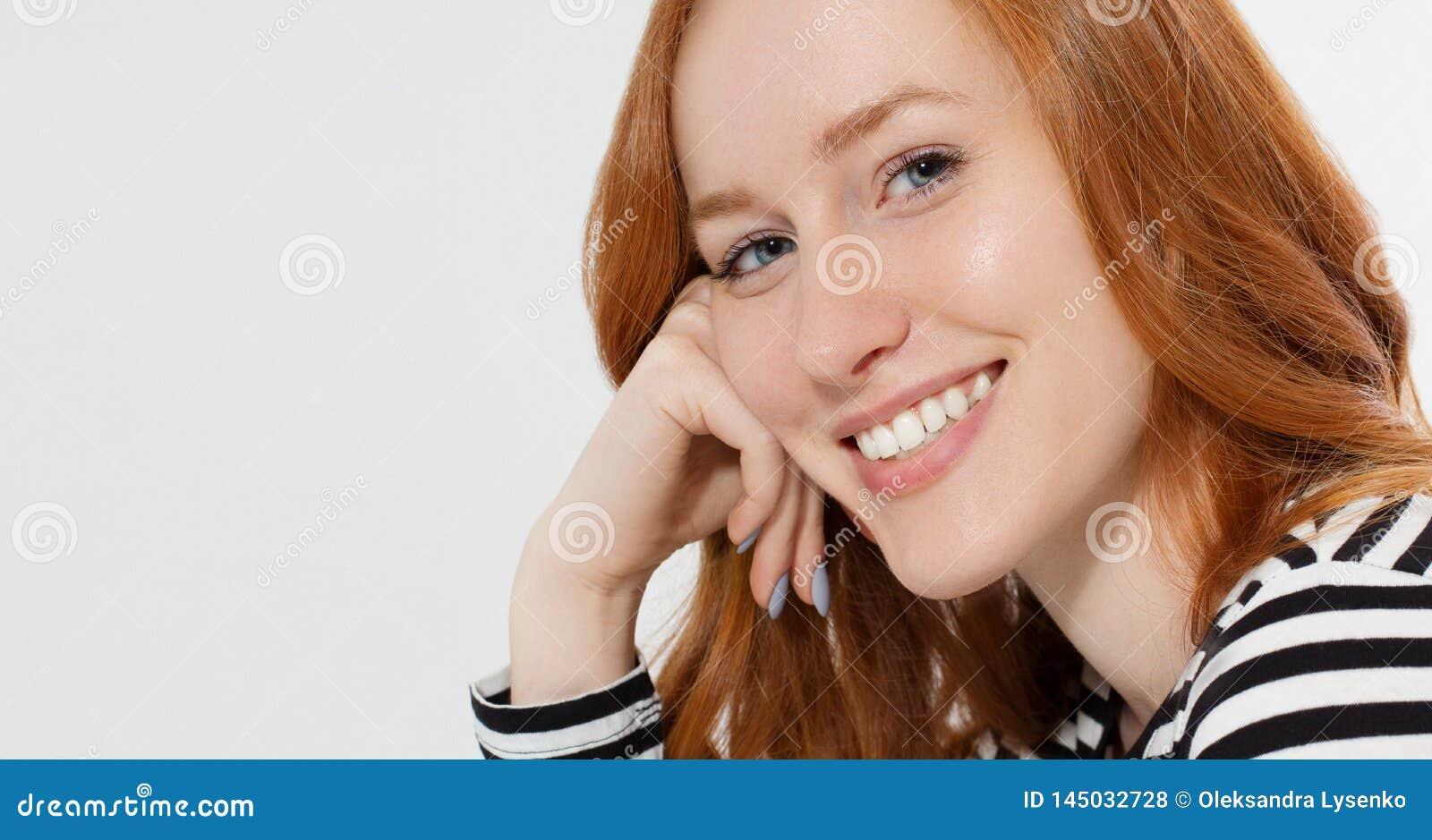 La muchacha pelirroja con cierre encima de la cara macra y los dientes blancos perfectos sonríen en el fondo blanco Belleza de la