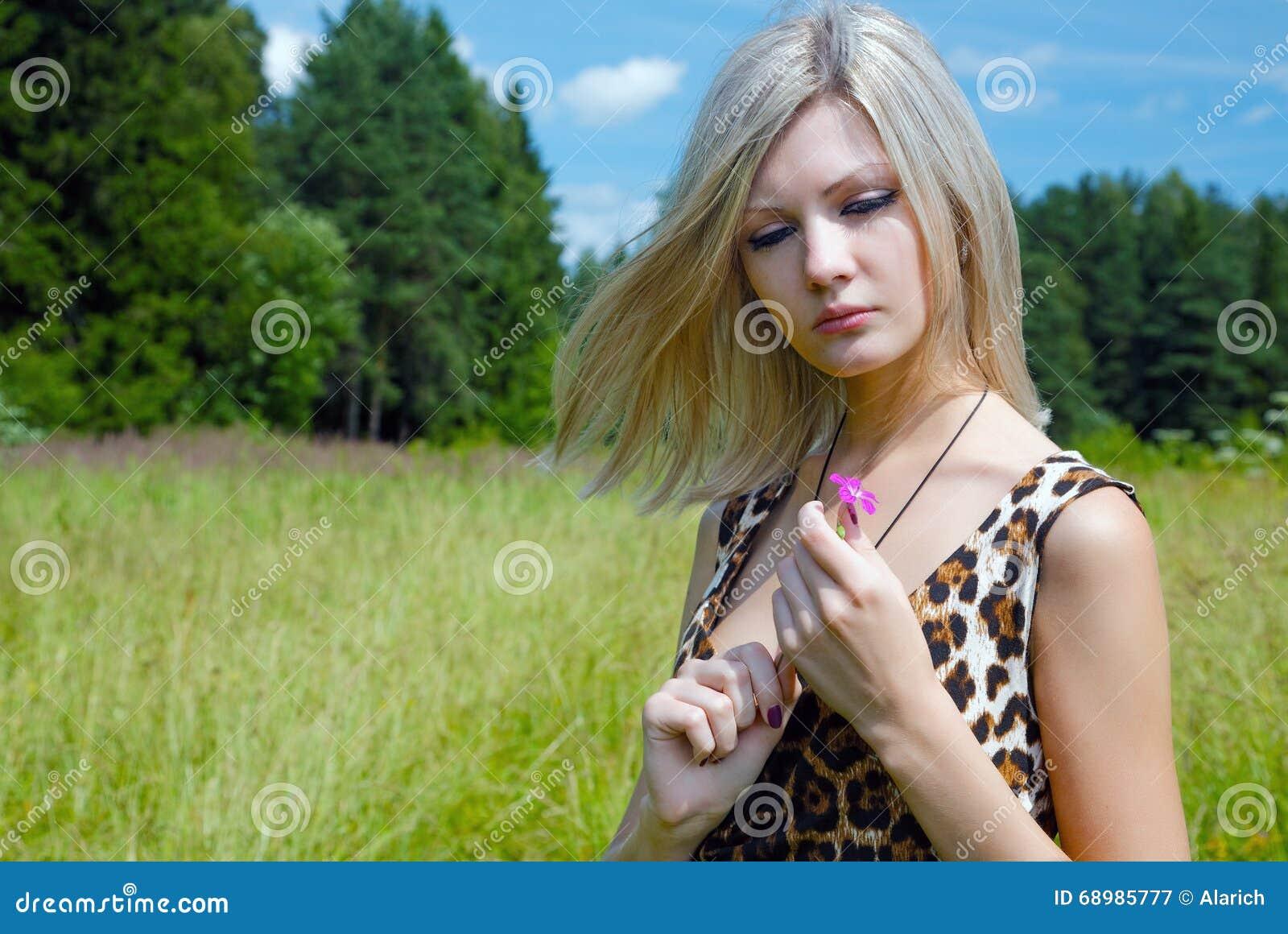 La muchacha pensativa con una flor del campo