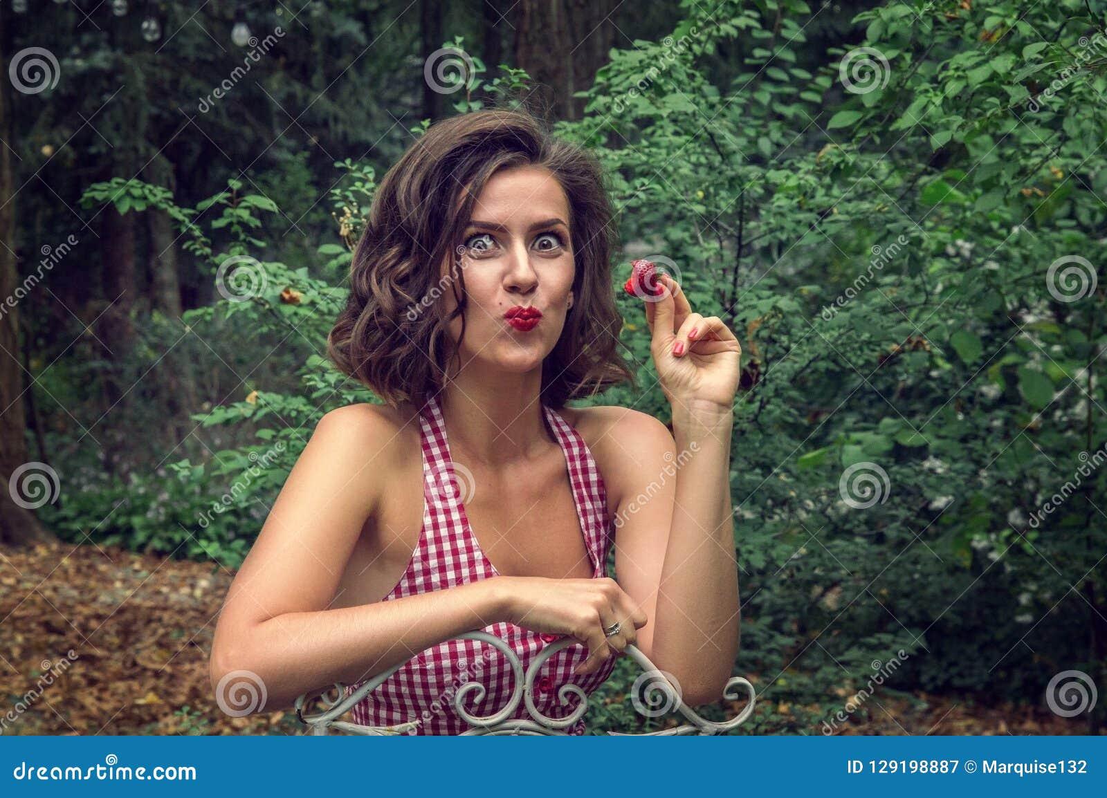 La muchacha Pin-para arriba come la fresa roja En la cara hay un placer y un placer emocionalmente exhibidos